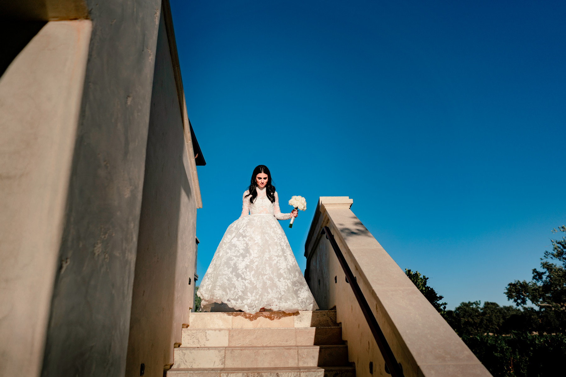 Bride descending stairs in long sleeve romantic lace ballgown - photo by John and Joseph - Los Angeles