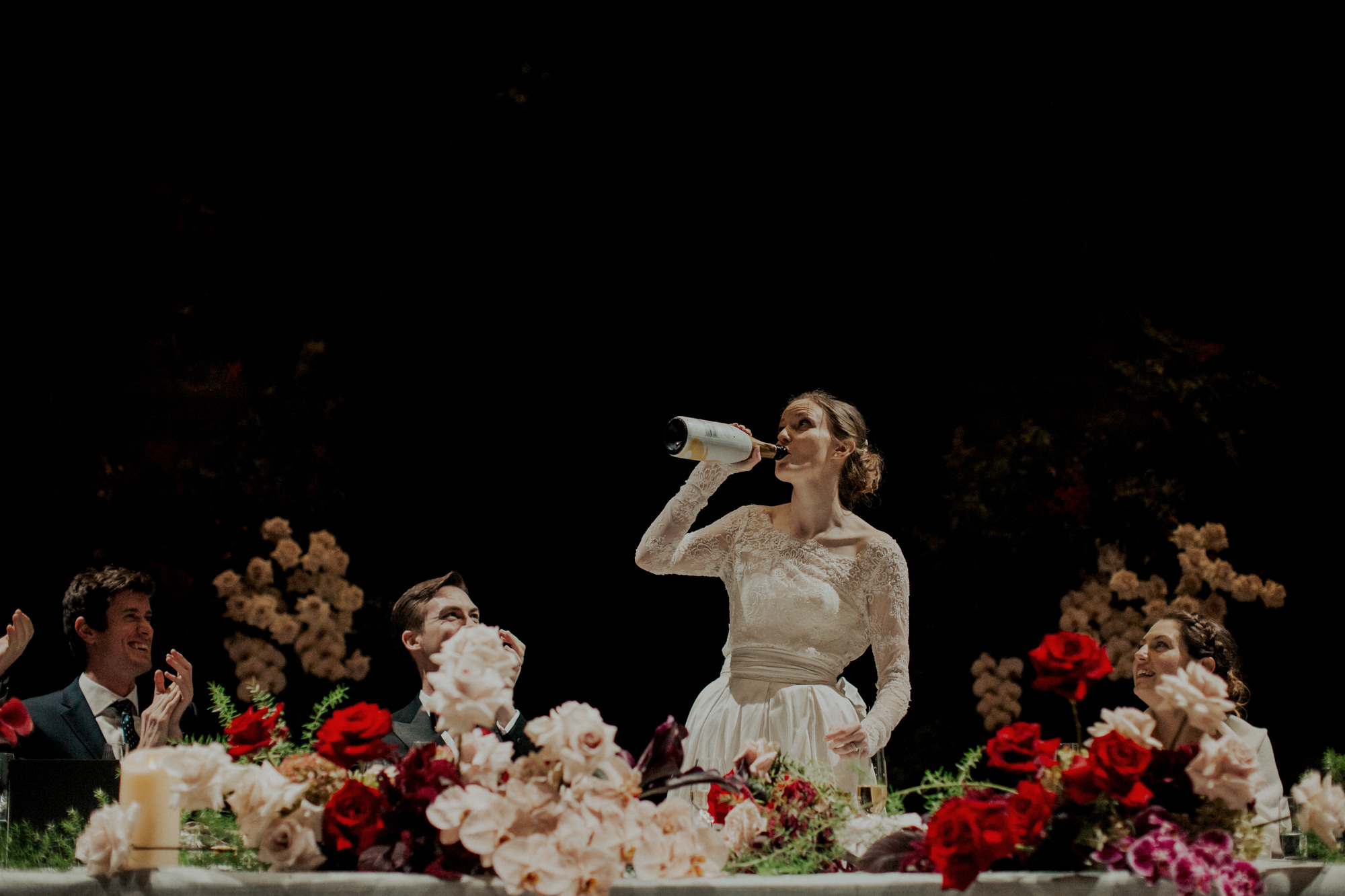 Bride drinking from champagne bottle during toasts, by Dan O'Day