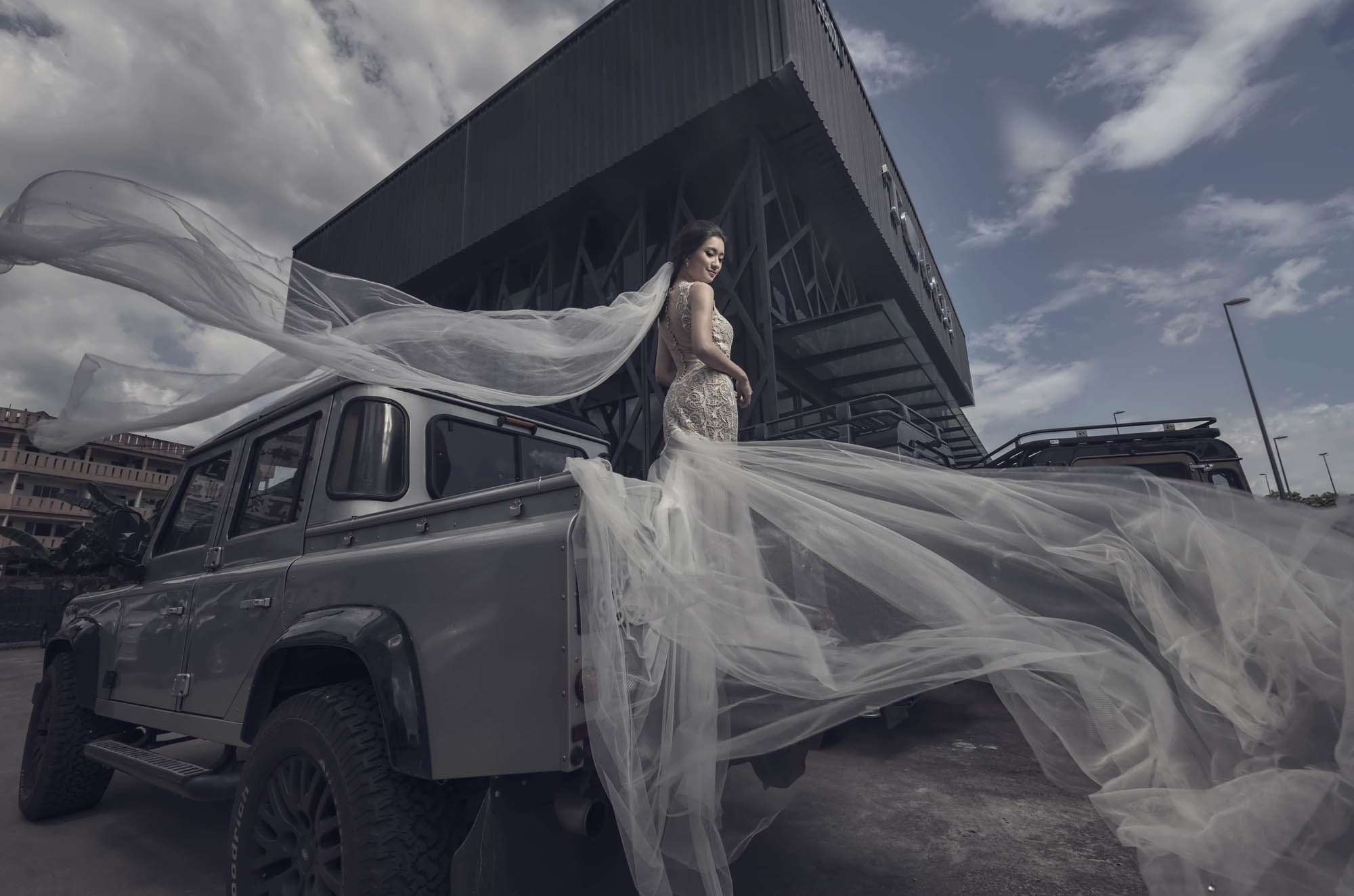 Bride with dramatic flowing veil and train standing on truck, by CM Leung