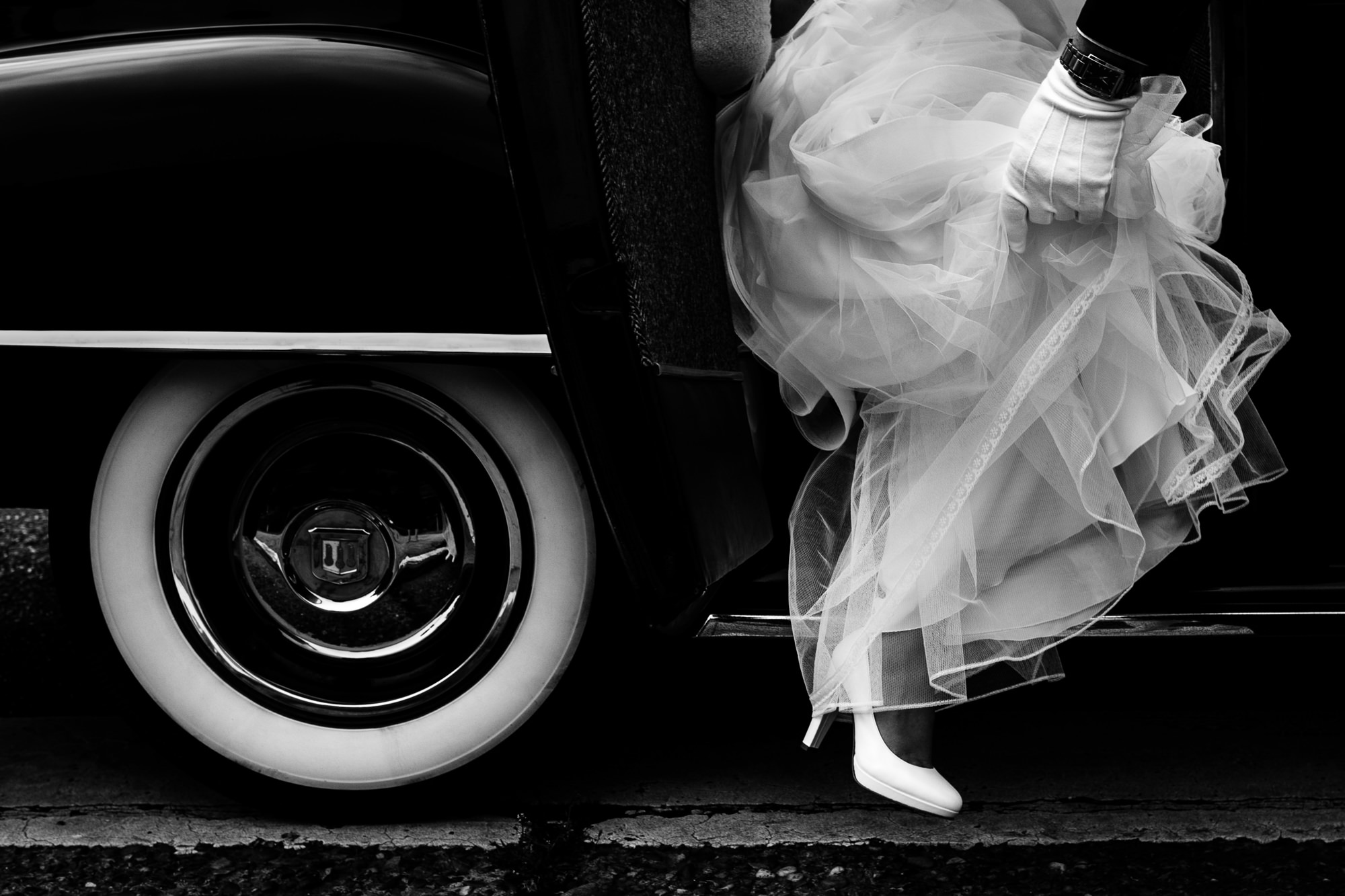 Bride in ruffled dress gets out of Antique car photo by Yves Schepers