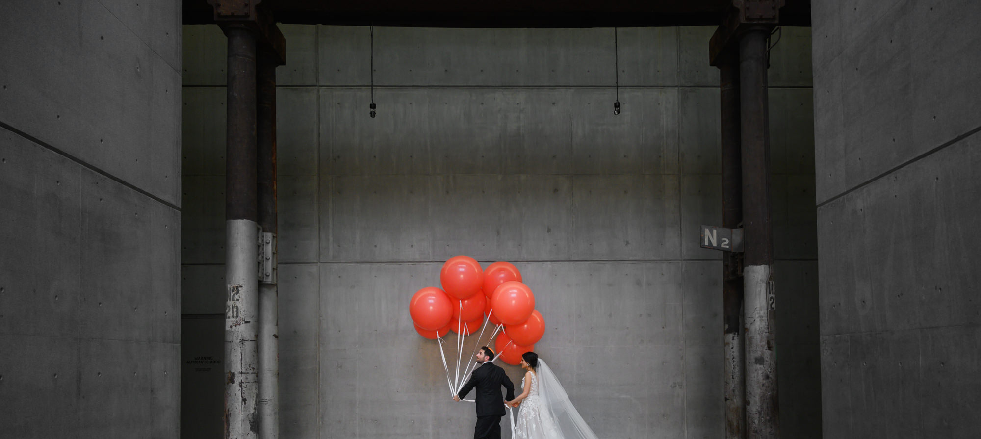 Couple on the way to reception with big red ballons - Studio Impressions Photography