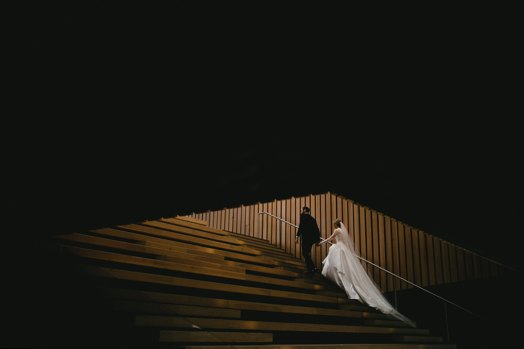 Bride and groom ascend stairs - photo by McClintock Photography Agency