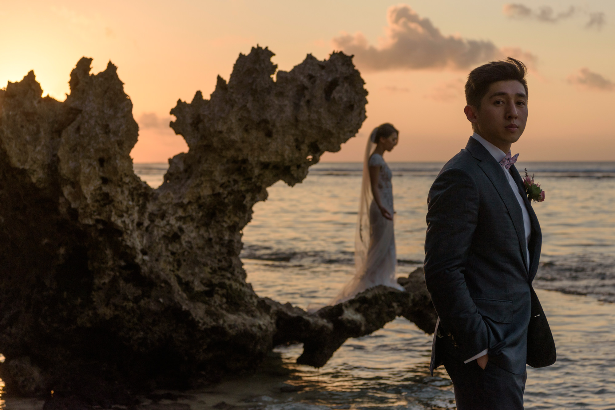 Portrait of groom during pastel sunset with bride in background  - Studio Impressions Photography