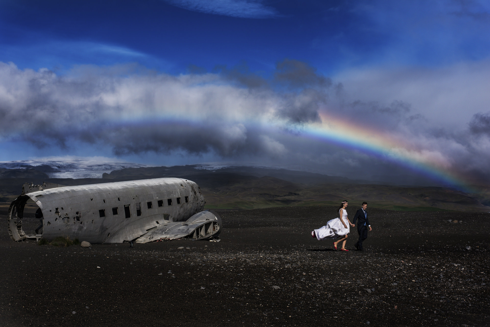 Bride and groom at plane wreck with rainbow - photo by Look Fotographica