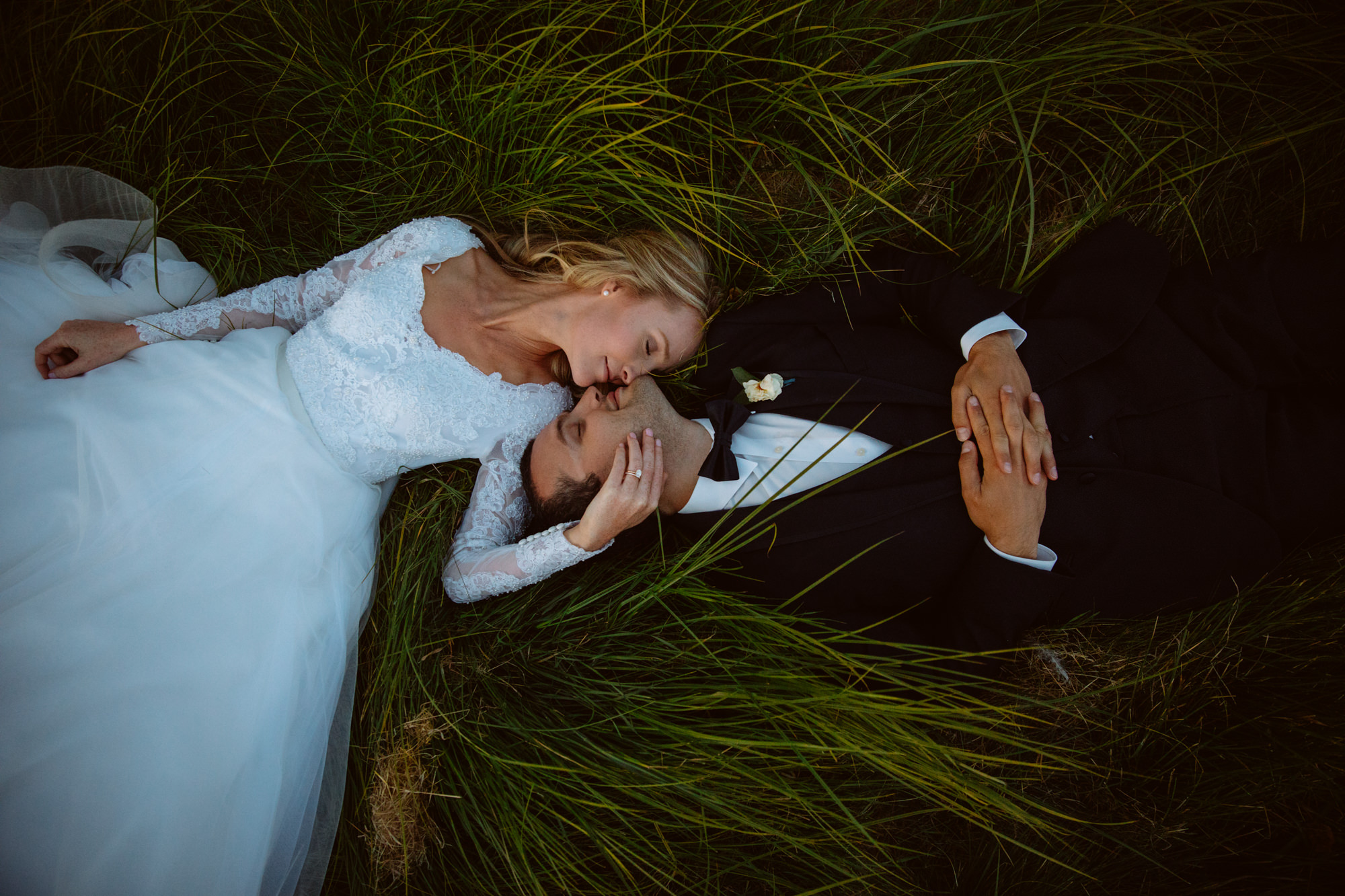 Couple lying the grass kissing - Jessica Hill Photograph