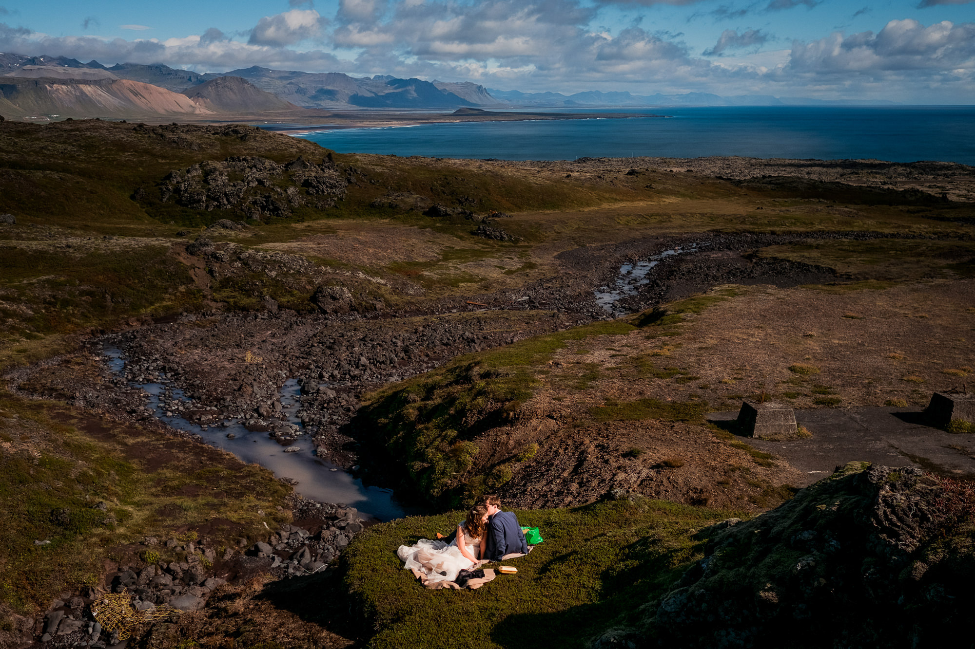 Bride and groom picnicking on rolling hills by the sea, by Nordica