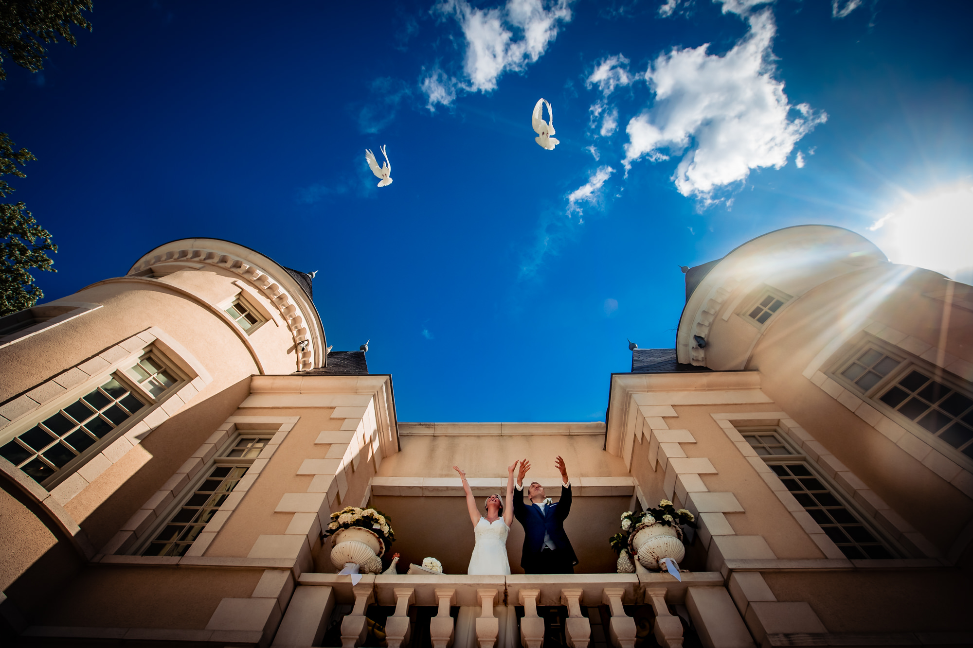 Bride and groom release doves from balcony, by Eppel Fotographie