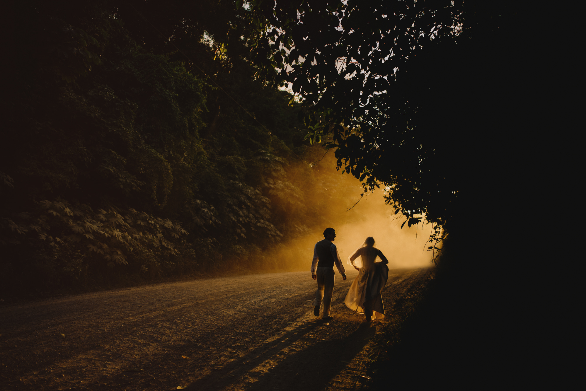 Bride and groom run down foggy road - photo by McClintock Photography Agency