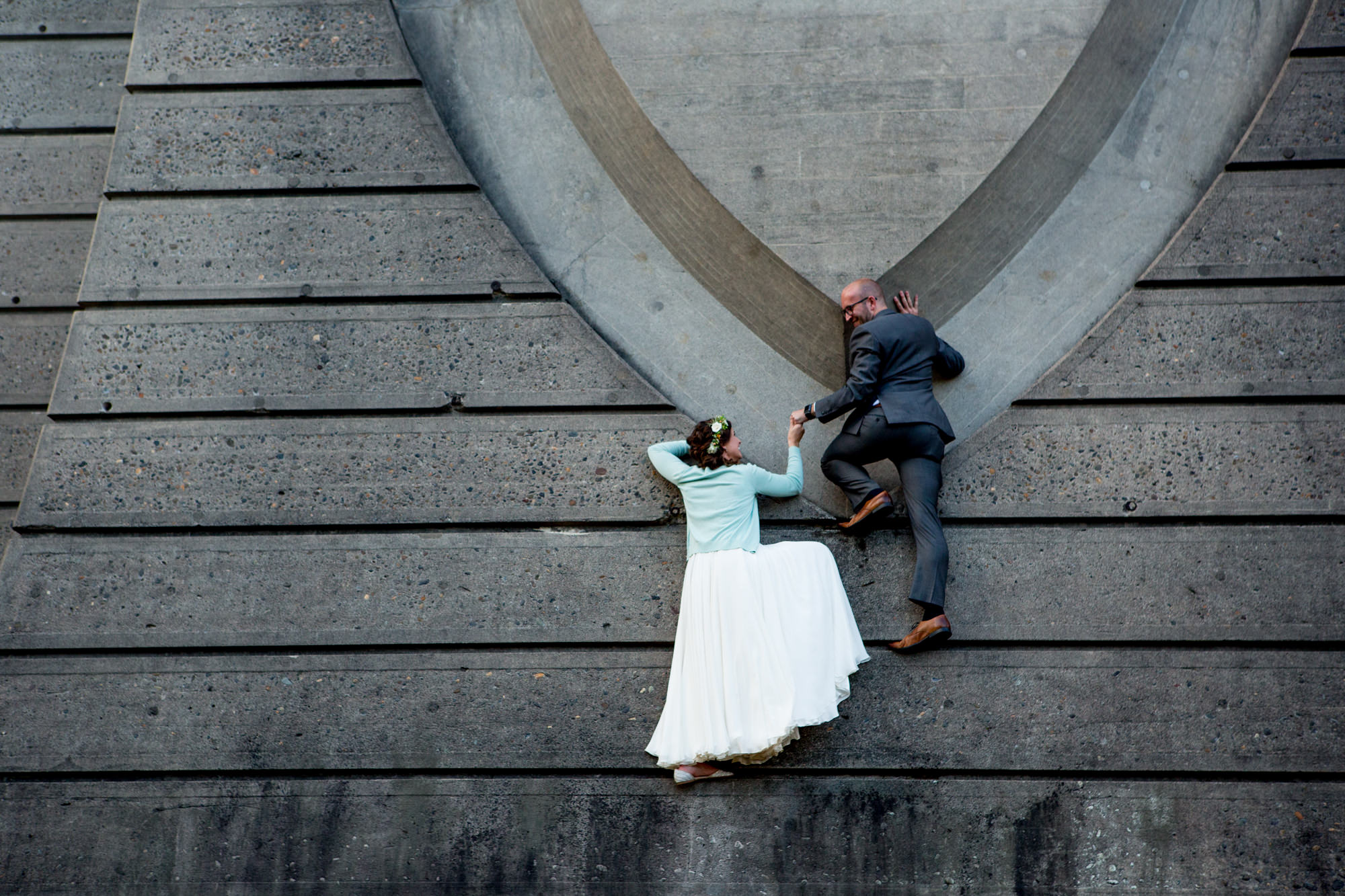bride and groom on ground look like they are climbing - Jessica Hill Photog