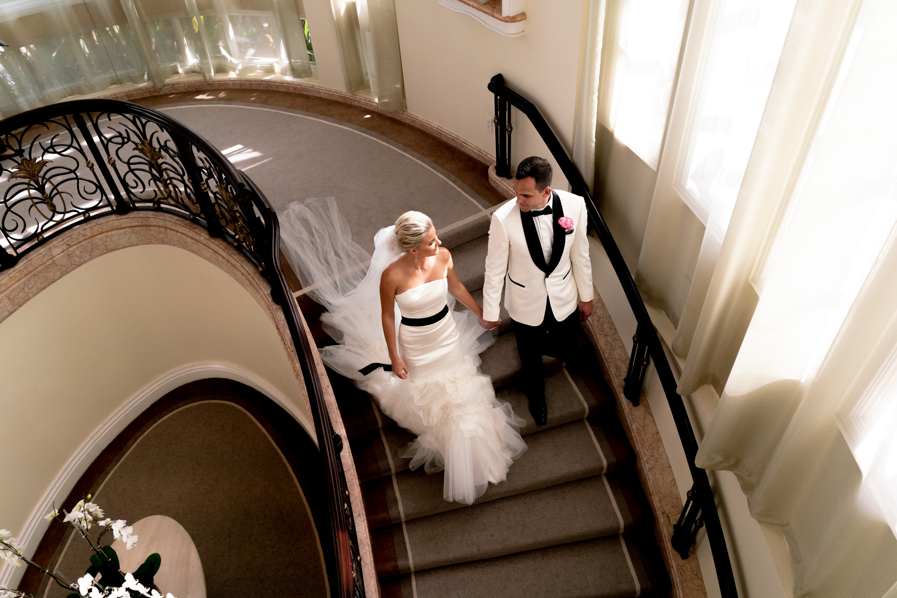 Bride and groom descending stairs in column dress with ruffled tulle skirt - photo by John and Joseph