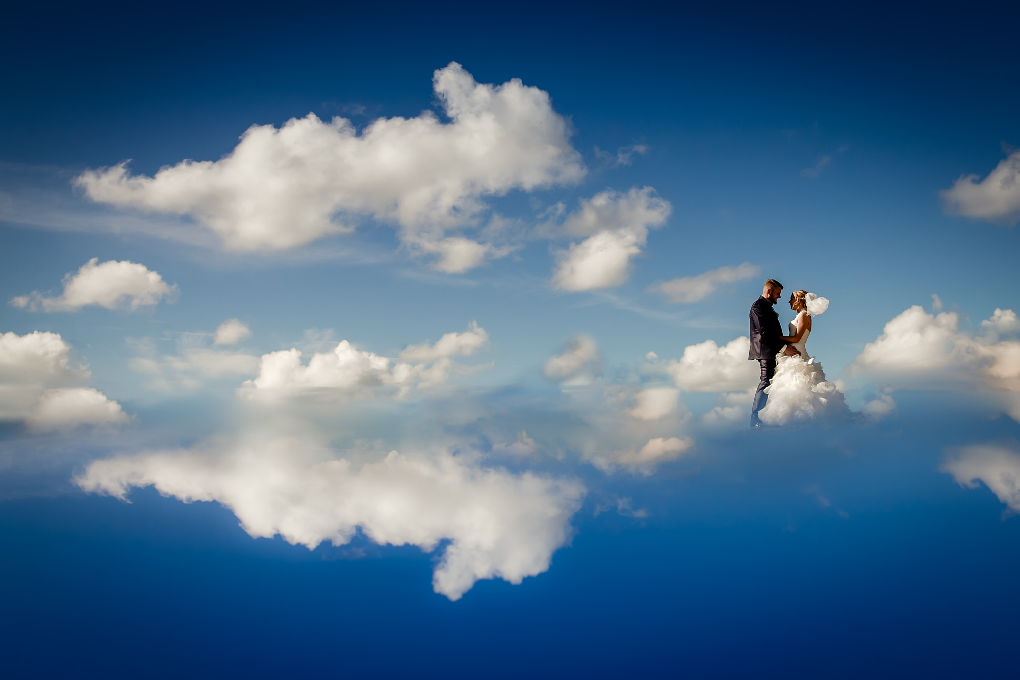 Epic bride and groom portrait floating on clouds, by Eppel Fotographie