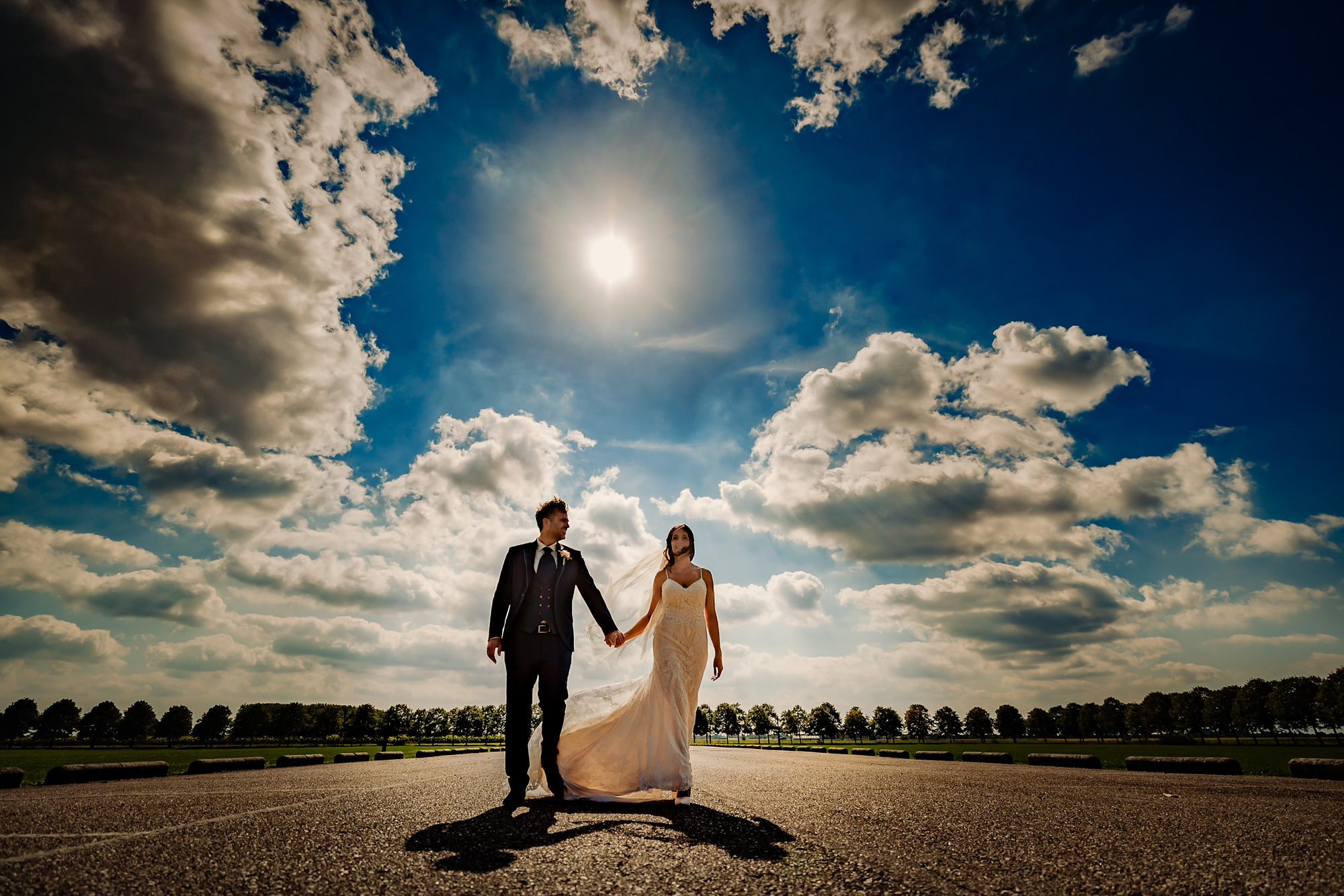 Bride and groom walking against blue sky photo by Eppel Photography