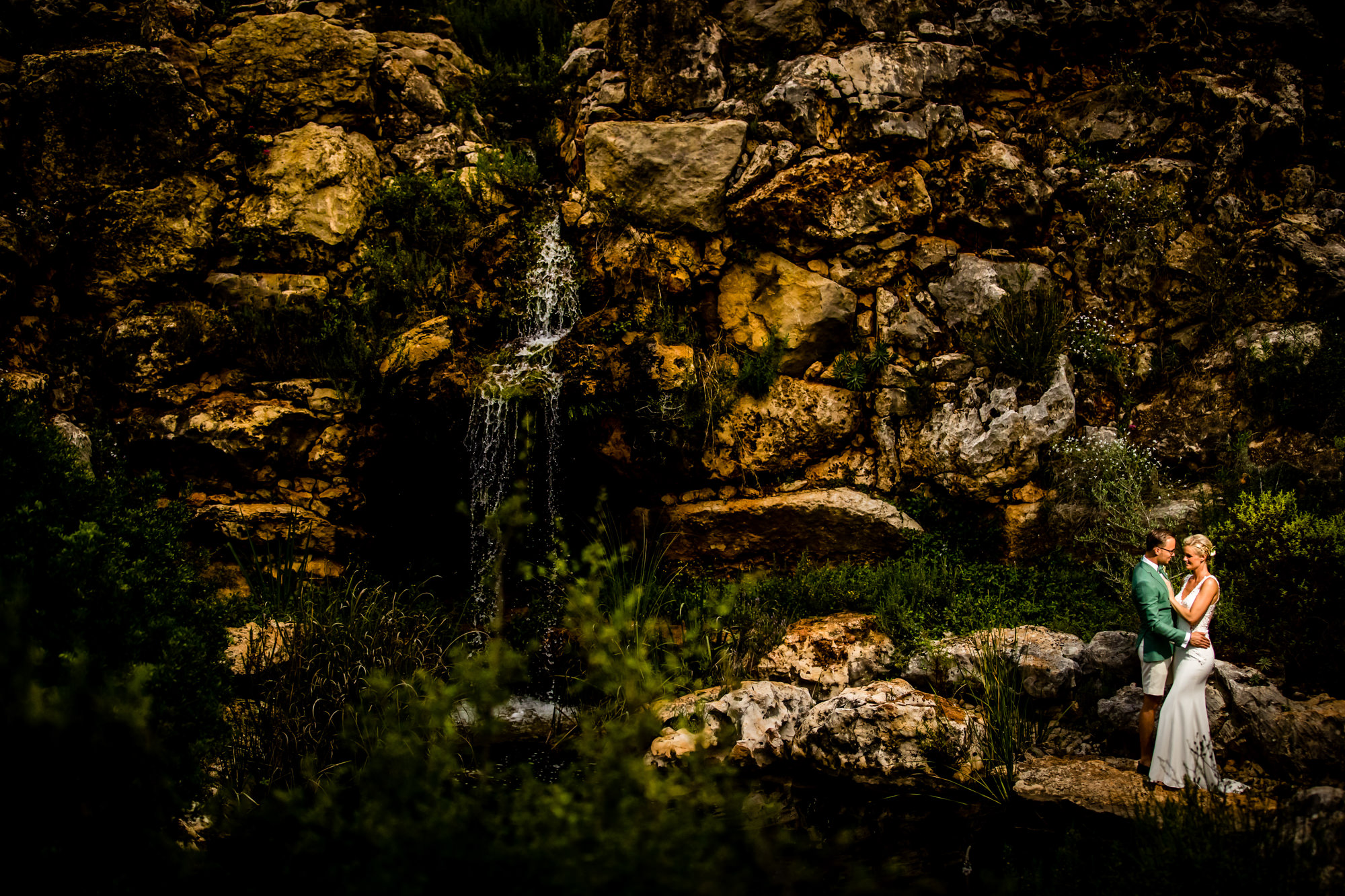 Couple near waterfall by Eppel Photography