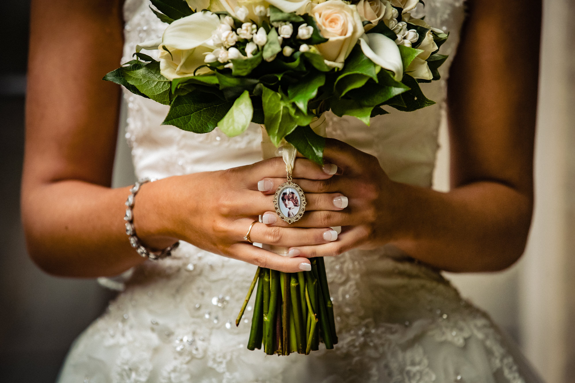 Bride holding bouquet with locket by Eppel Photography