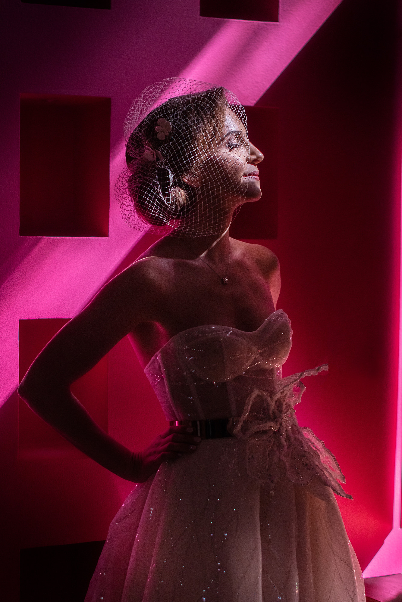 Bride in bright pink light with bird-cage veil and strapless beaded gown - Daniel Aguilar Photographer