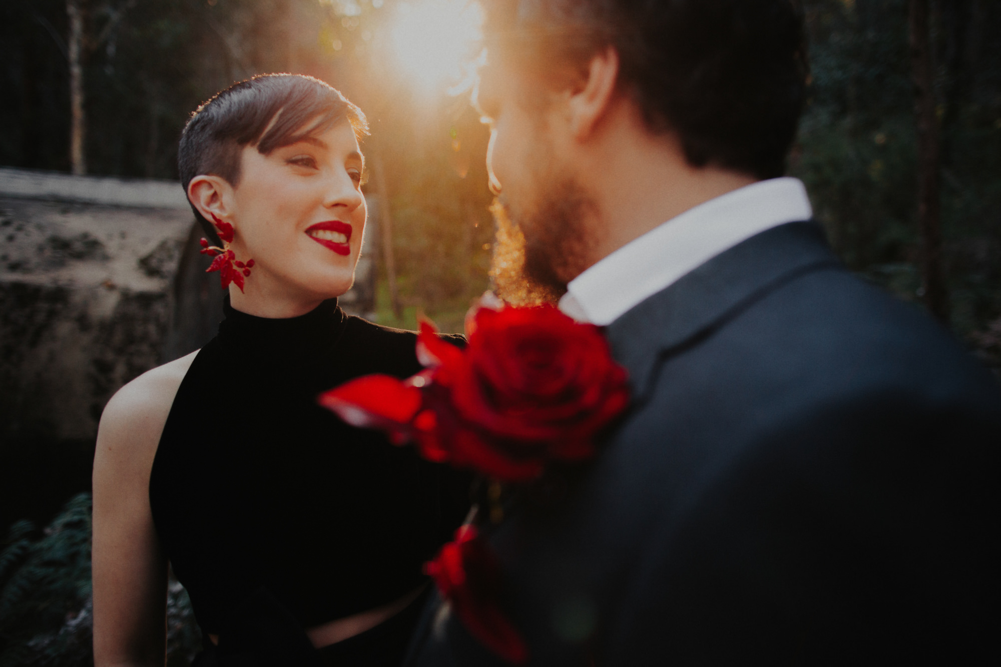 Bride in black dress with red accents with groom in golden hour  - photo by Dan O'Day