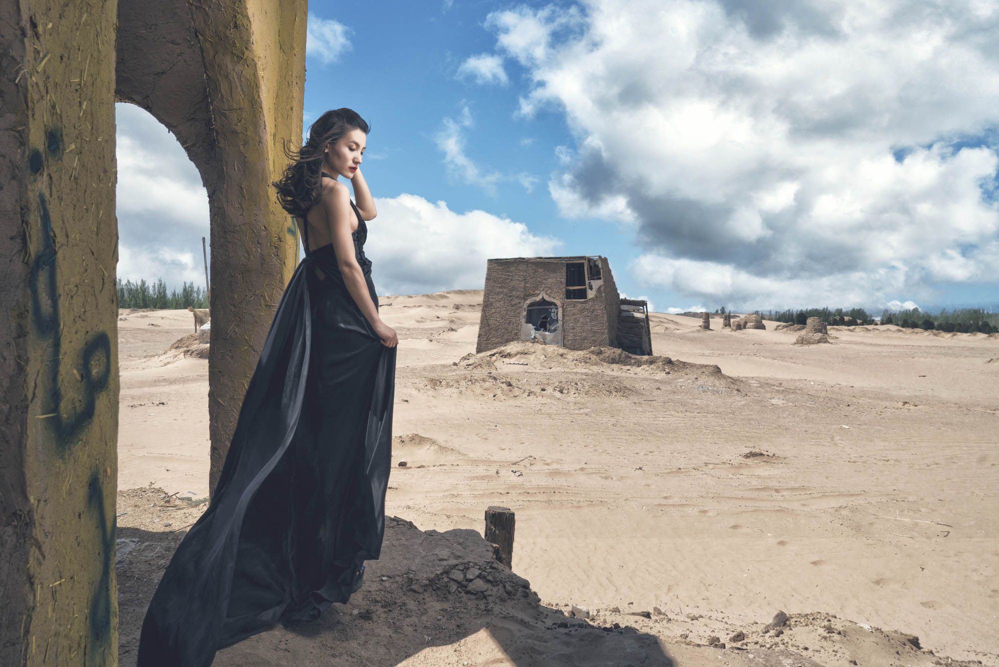 Bride in black gown standing in abandoned building in desert, by CM Leung