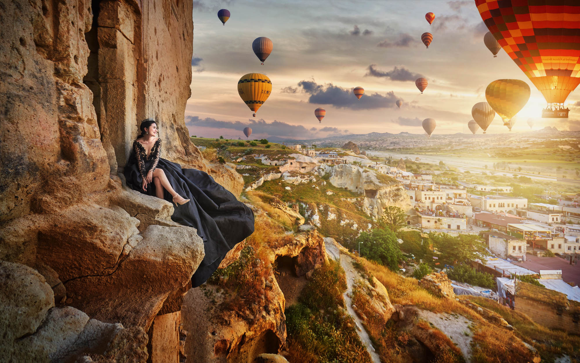 Bride in beautiful black lace gown sitting on mountain cliff with hot air balloons in background, by CM Leung