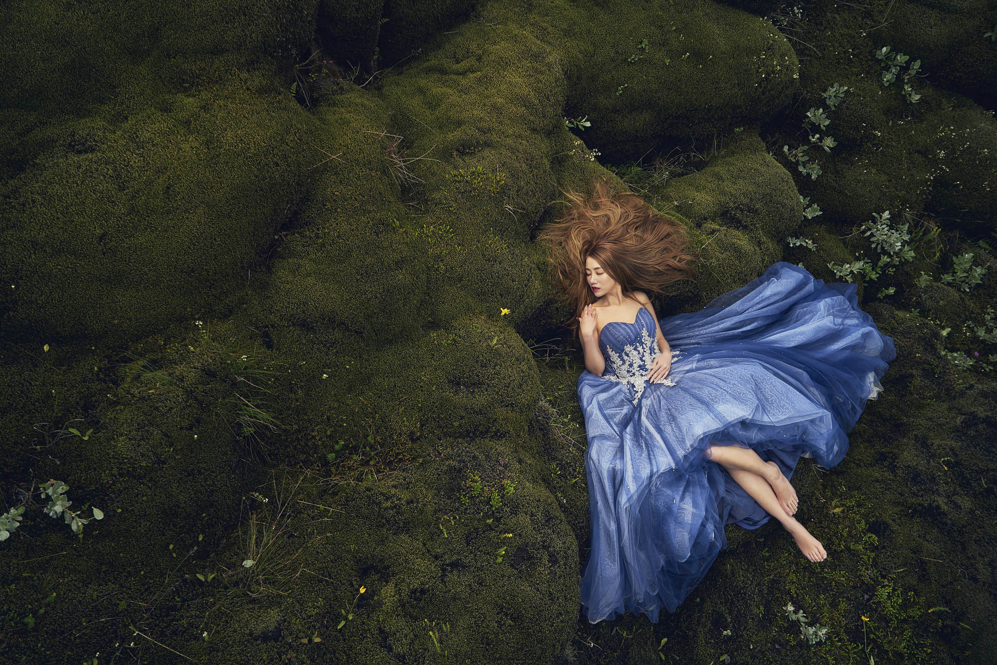 Bride in blue gown laying on field of moss, by CM Leung