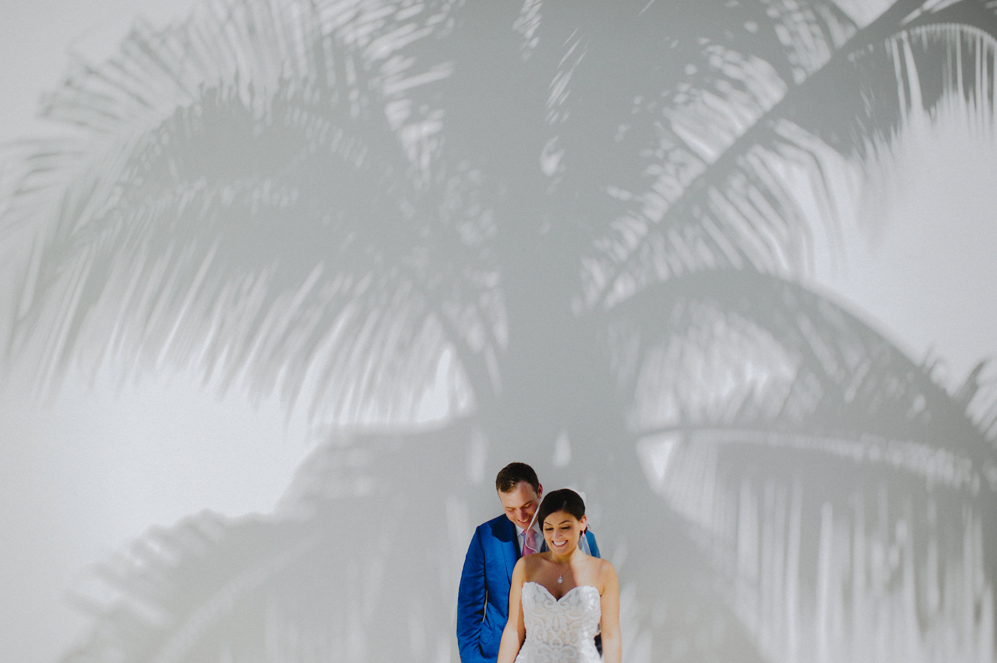 Couple against shadow of palm tree by Fer Juaristi
