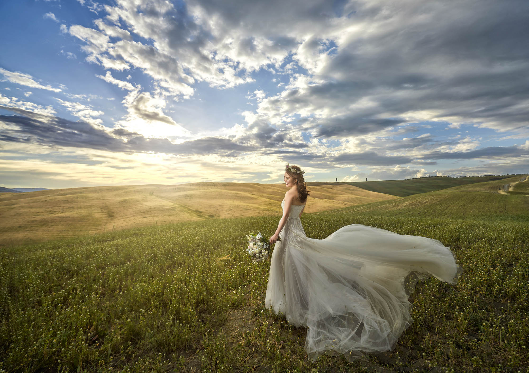 Bride in flowing tulle gown in field of grass, by CM Leung