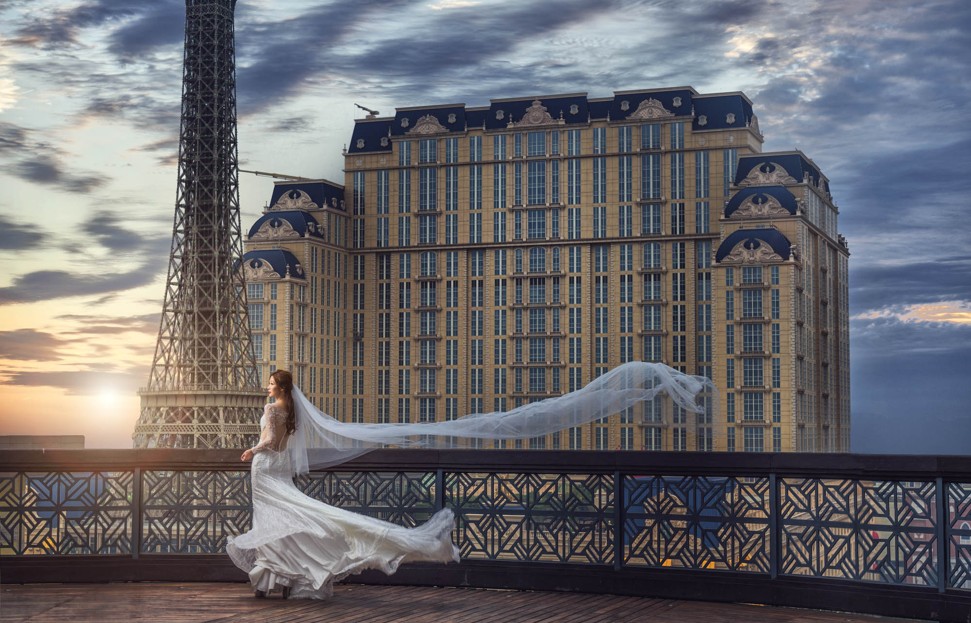 Bride with flowing veil next to Eiffel Tower, by CM Leung