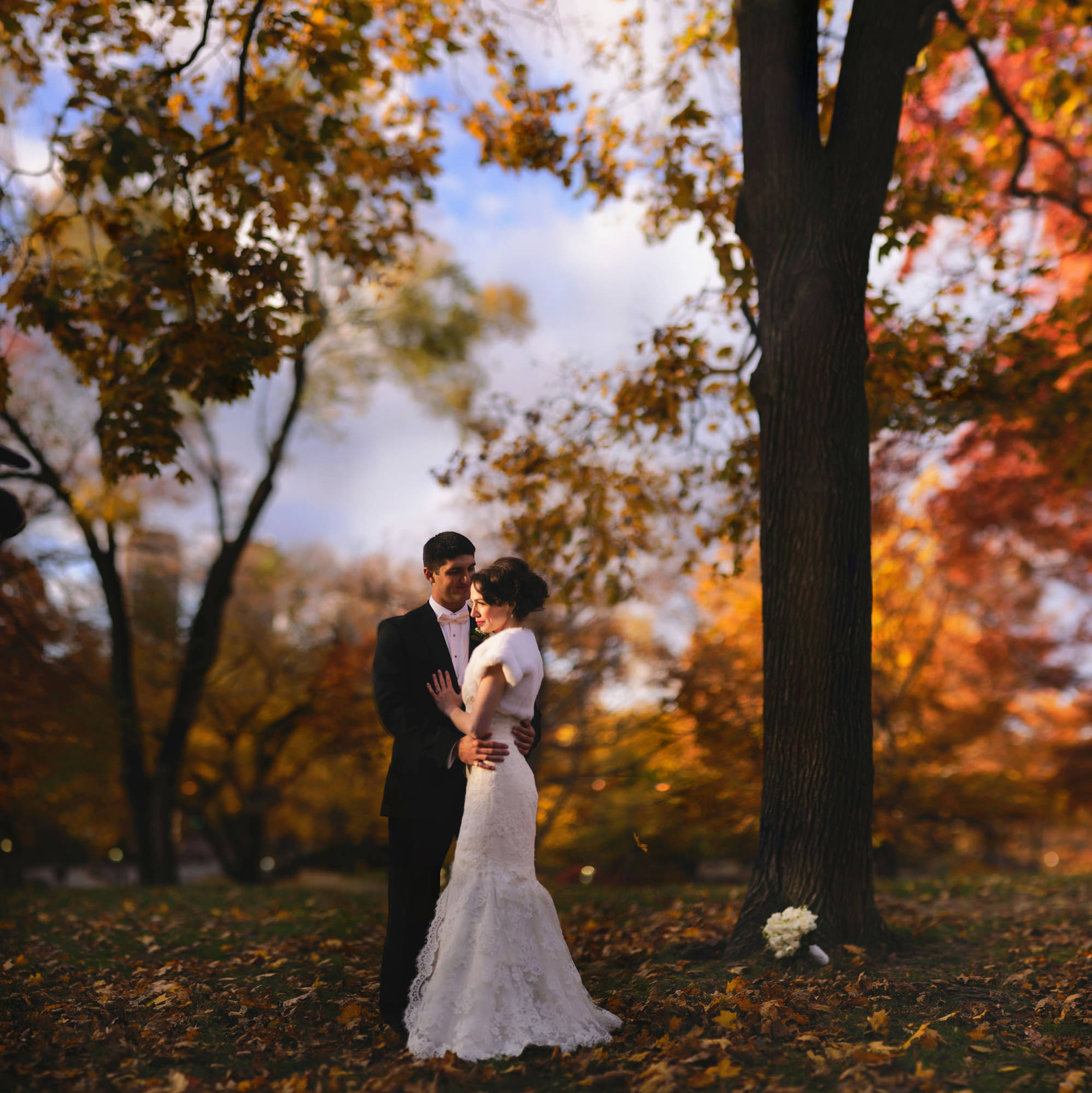 Fall portrait of bride in faux fur stole and groom in tux, photo by The Brenizers
