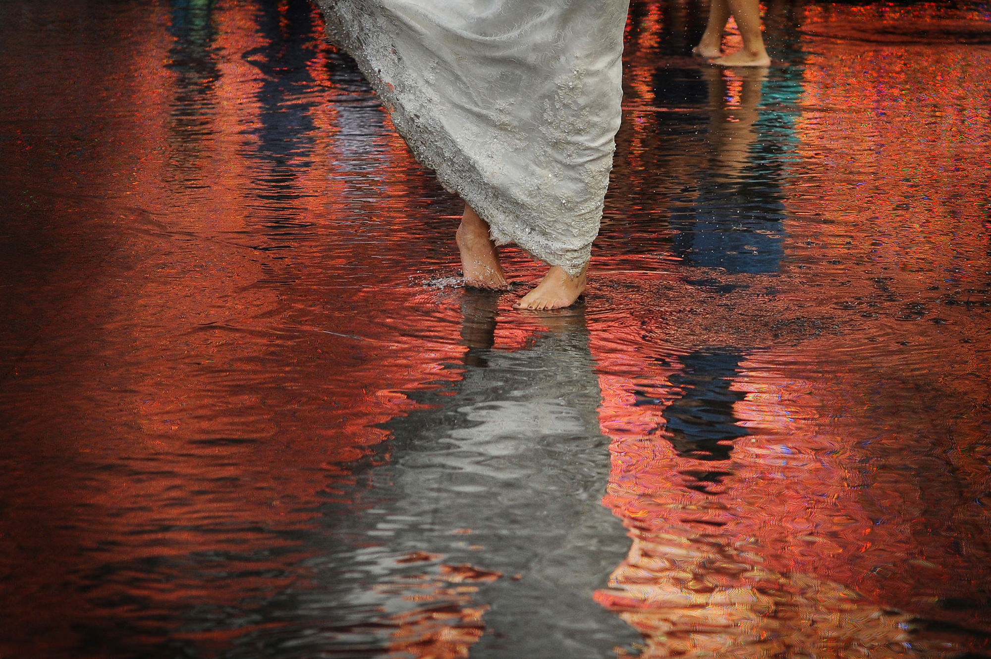 Bride in gown dancing barefoot in red reflection  - photo by Daniel Aguilar