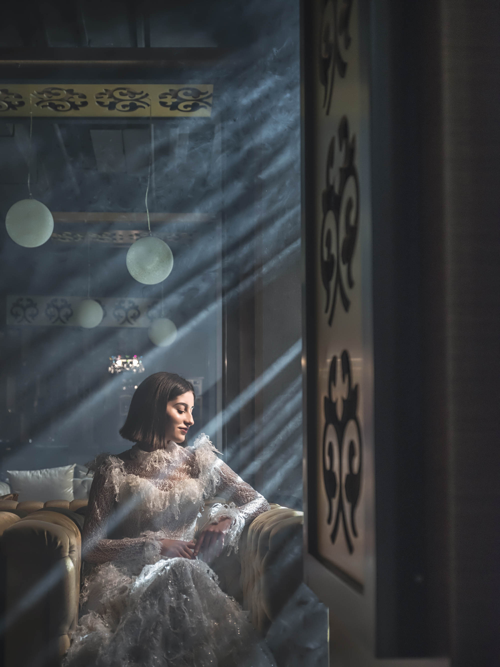 Bride in ornate long sleeve gown in dramatic window light, by CM Leung