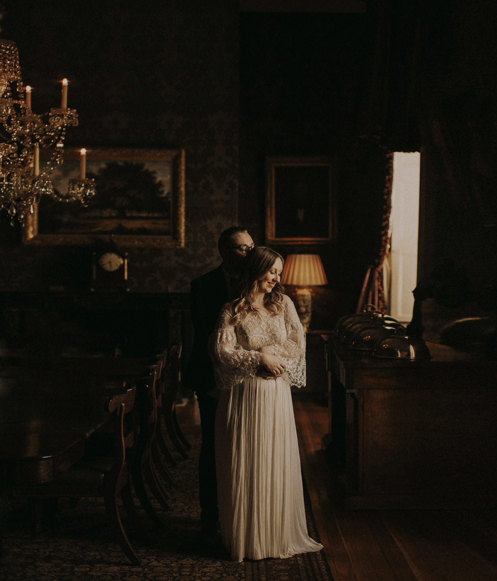 Bride and groom embrace in classically decorated room, by Dan O' Day