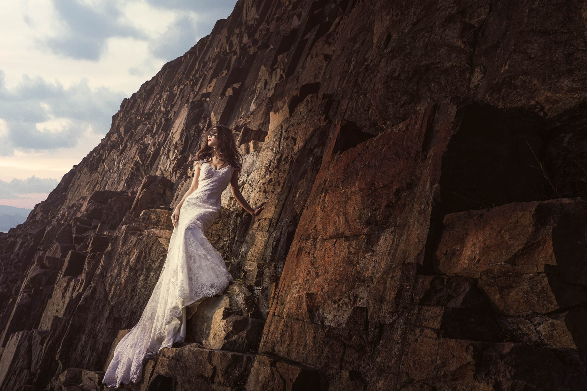 Bride in mask and white lace gown standing against rock cliff, by CM LEung
