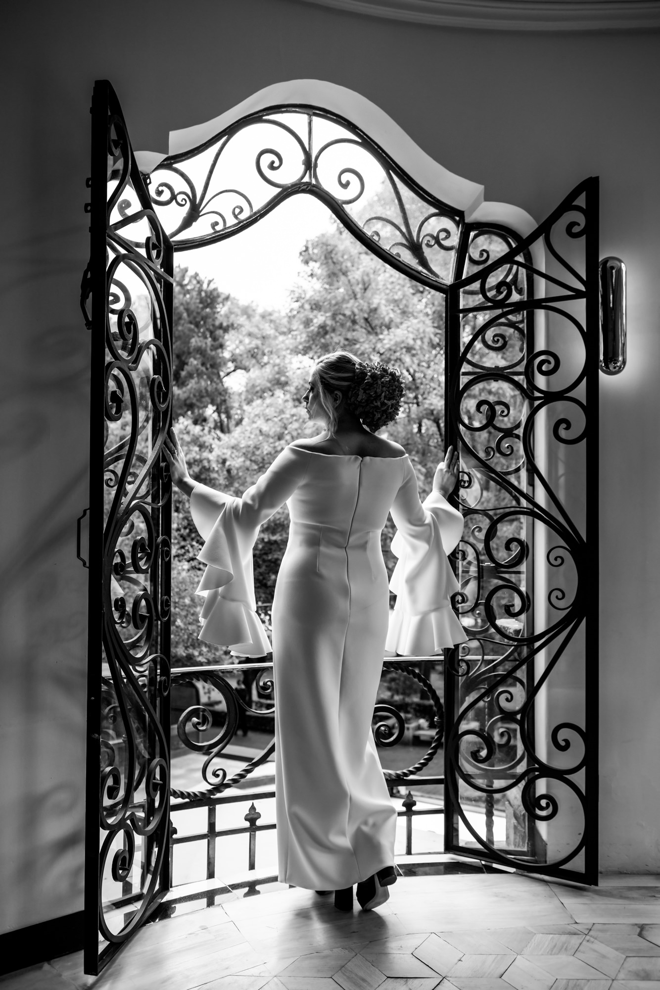 Bride in modern sheath looks out Spanish wrought iron window - Morgan Lynn Photography