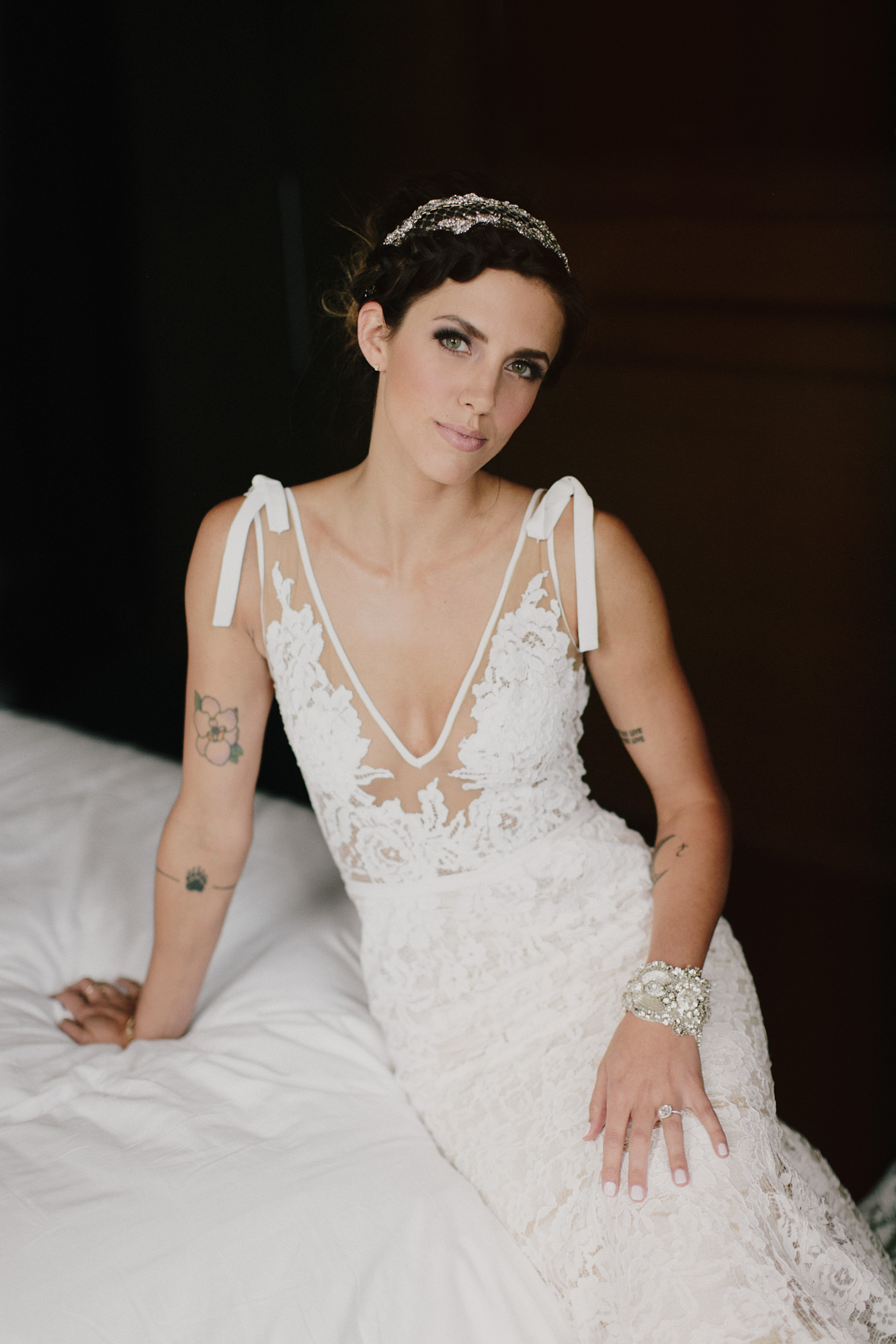 Bride in plunging sheer lace dress with ribbon shoulders by James Moes