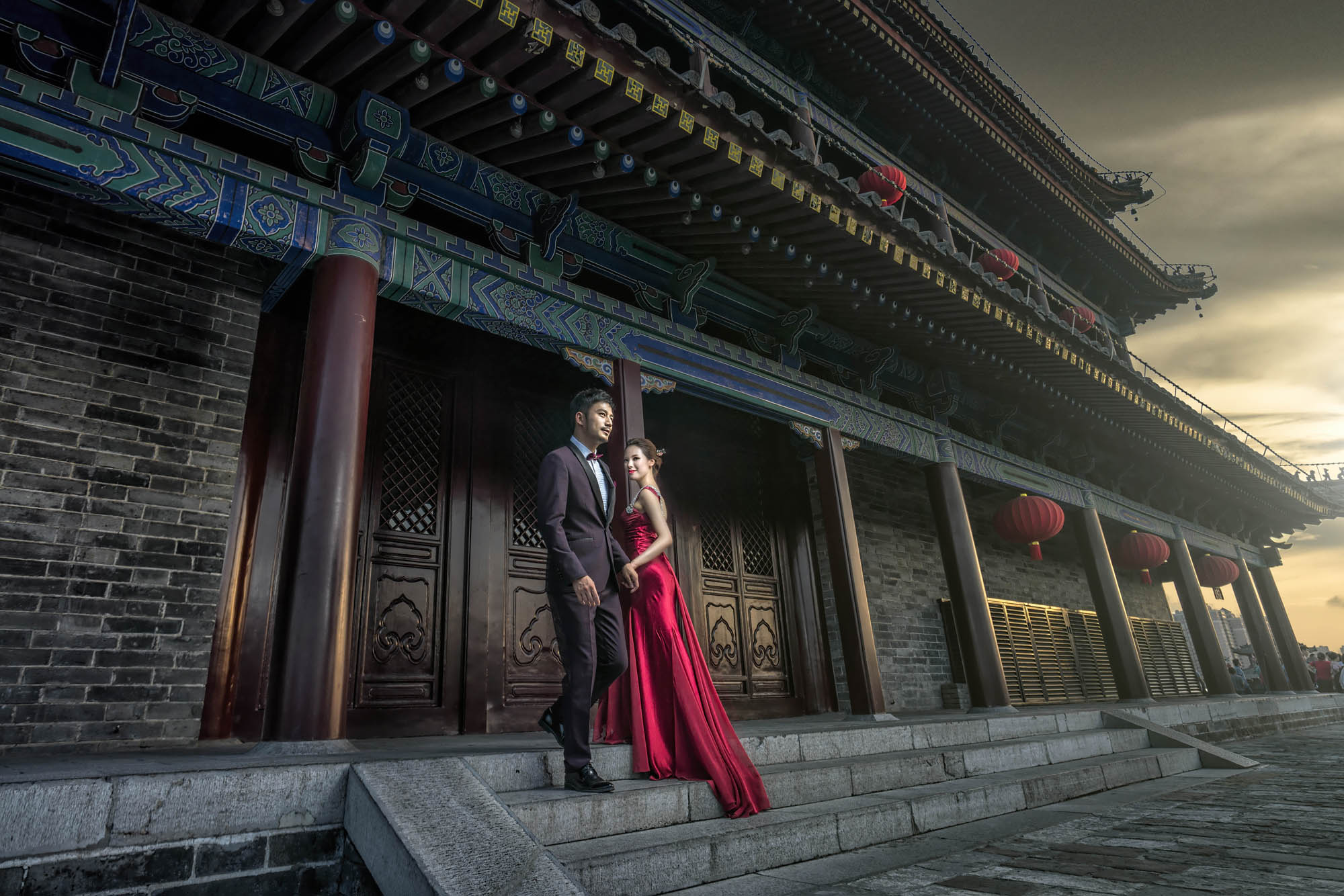 Bride in red gown with groom in tux in historic Chinese temple, by CM Leung