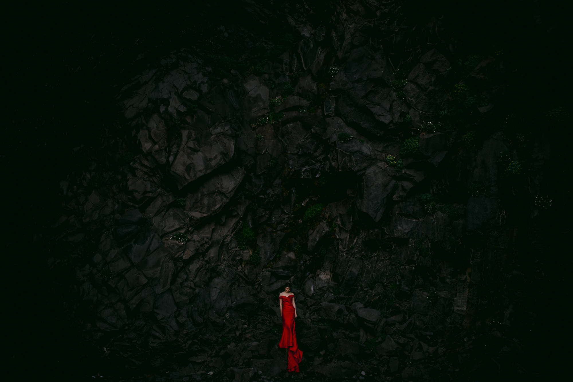 Bride in red satin A-line gown at black basalt cliff - photo by McClintock Photography Agency