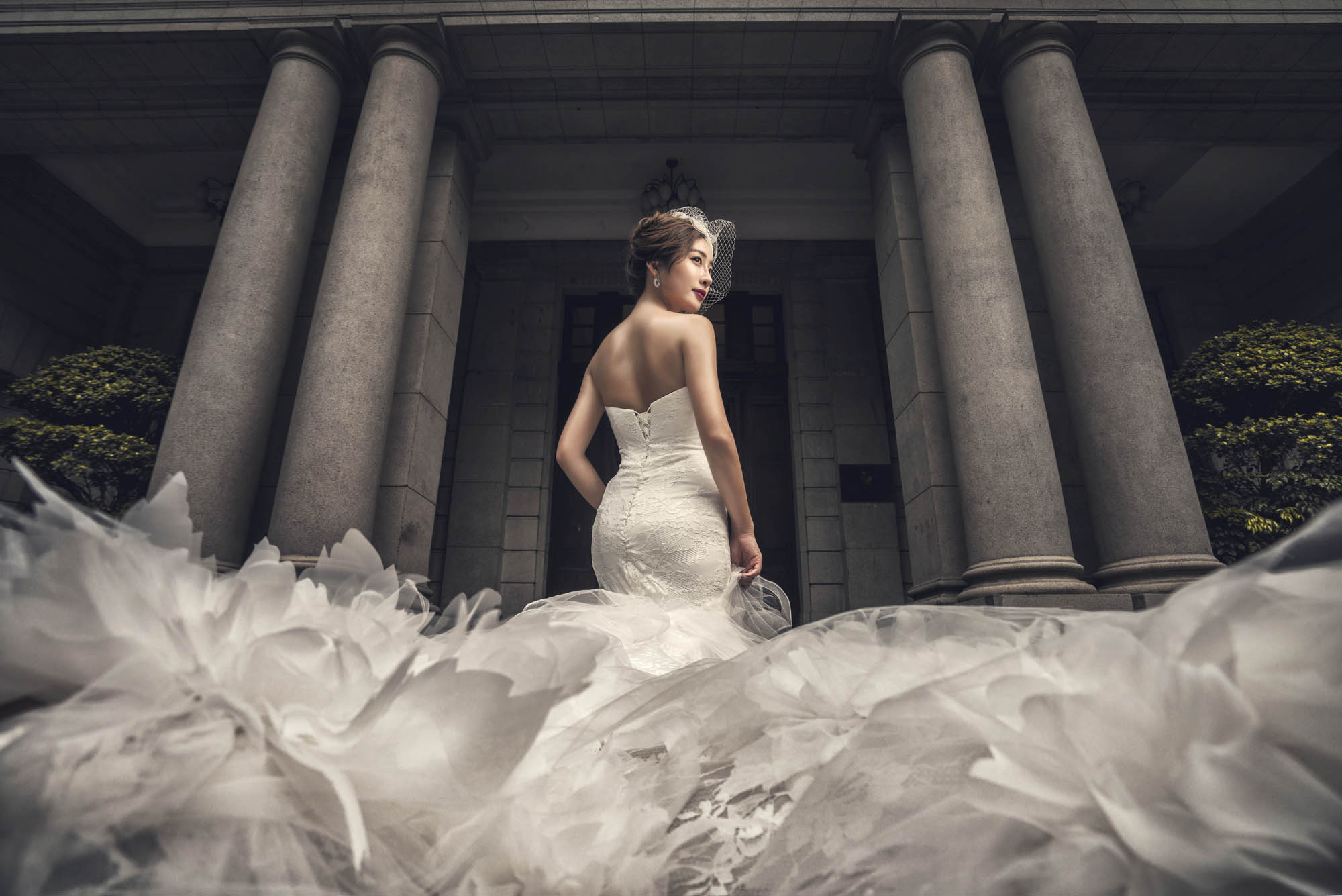 Bride in birdcage veil and epic feathered ballgown by Roman pillars, by CM Leung