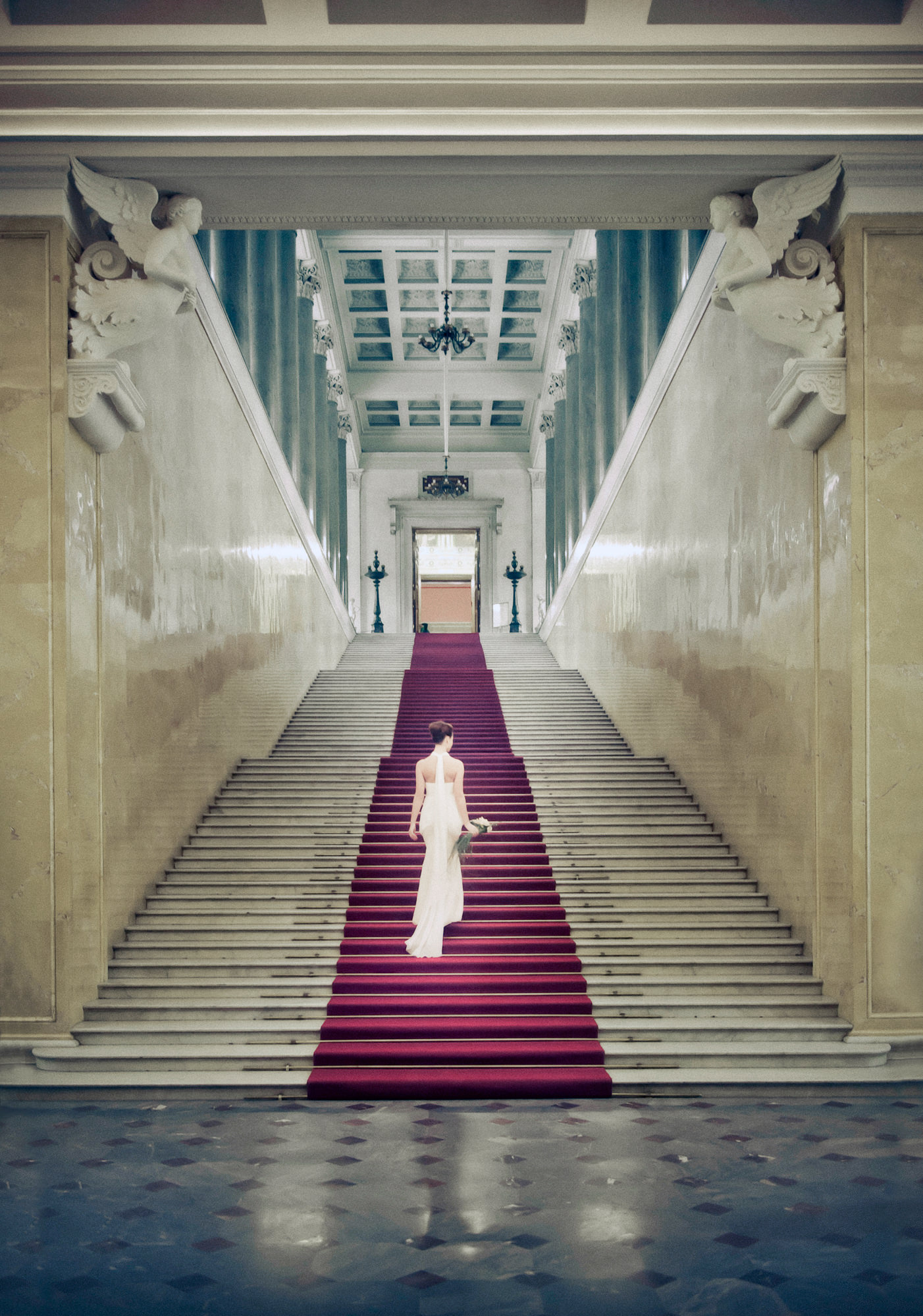 Bride in crepe column gown ascends red carpet up marble stairs -  Studio Impressions Photography