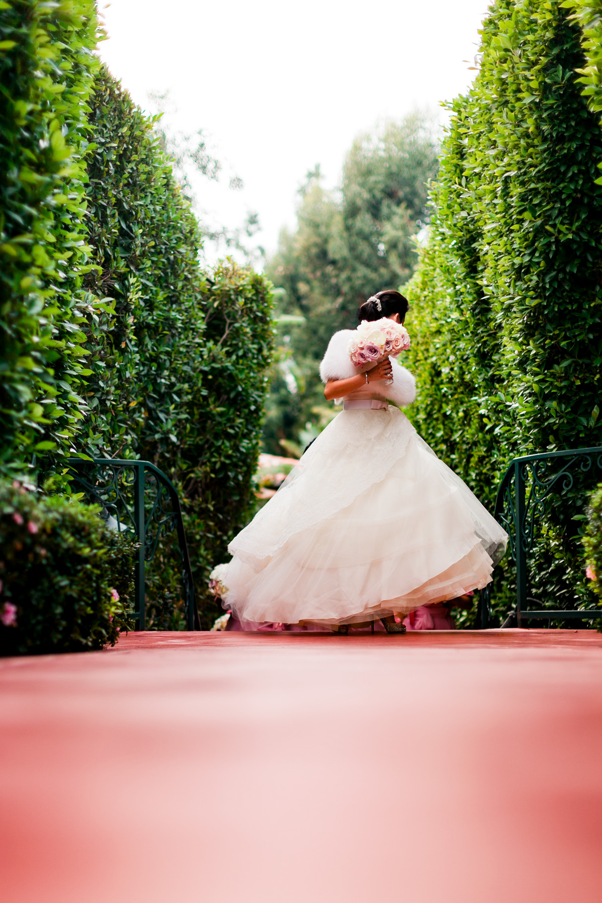Bride in swirling ballgown and fur wrap in hedge garden - photo by John and Joseph Photography