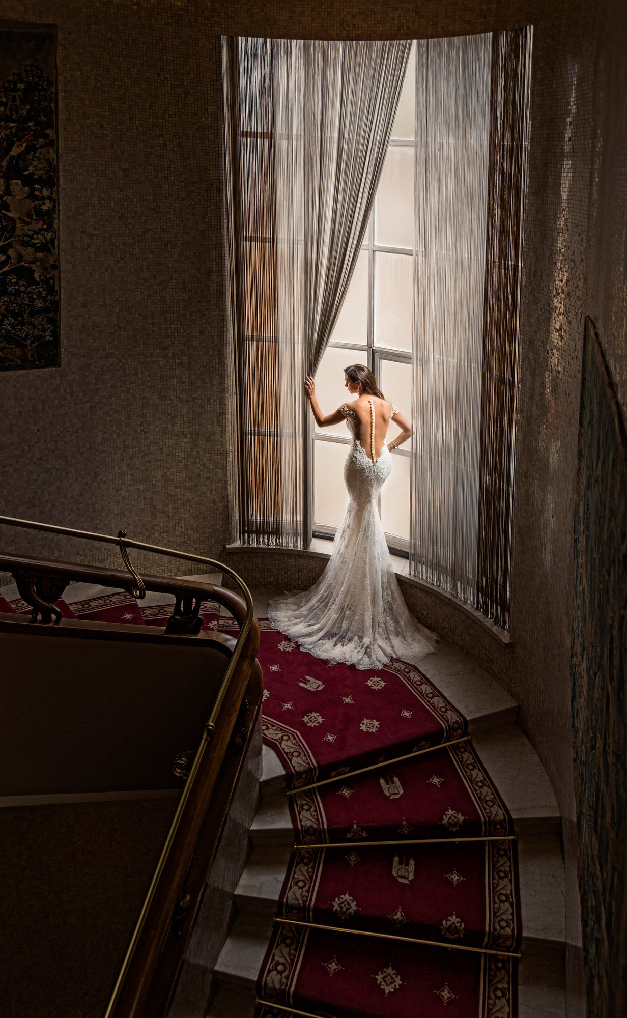 Bride in trumpet dress with sheer back in window - photo by Jerry Ghionis