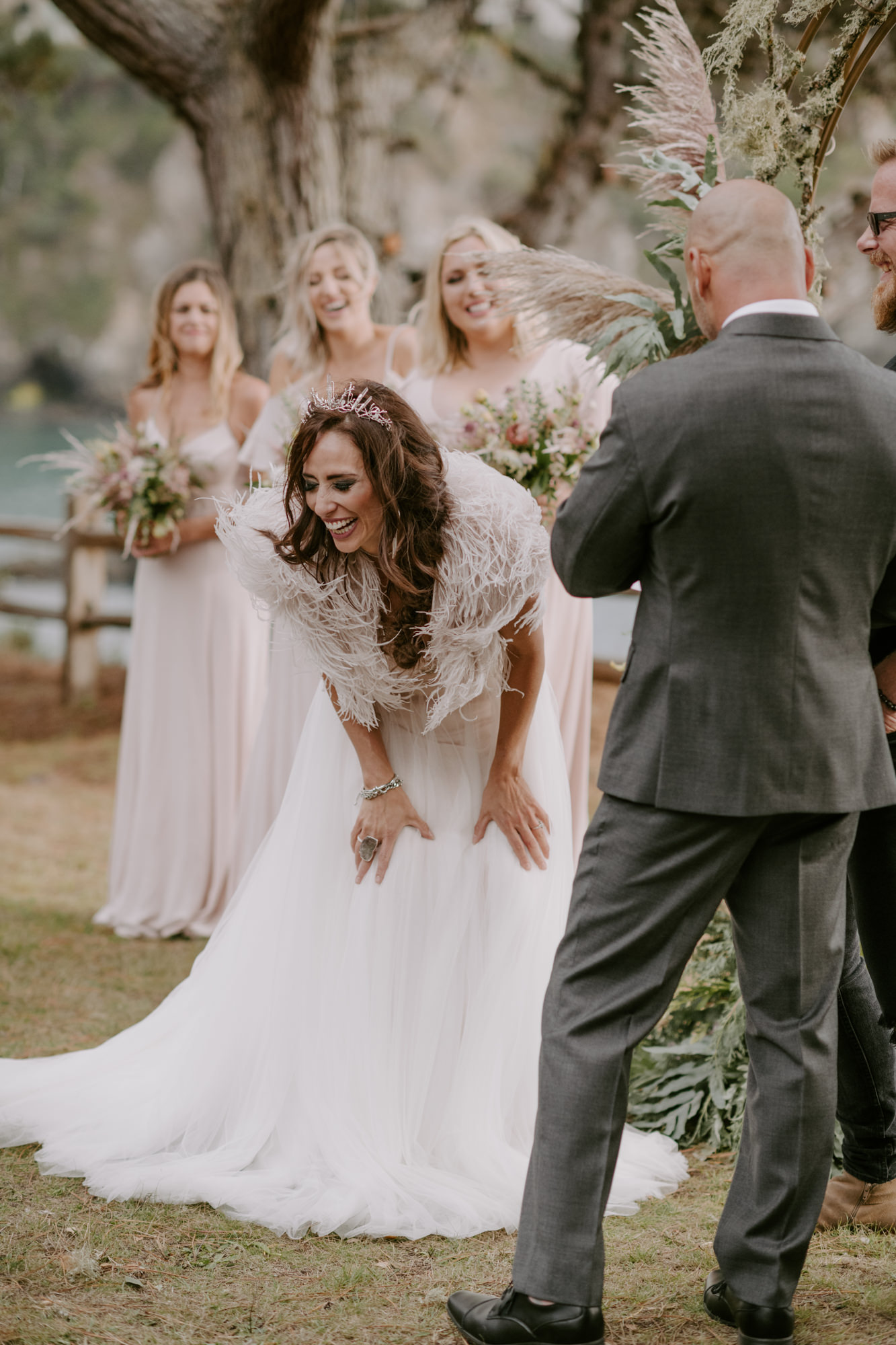 Bride laughing at ceremony with white feather shawl - photo by Kristen Marie Parker