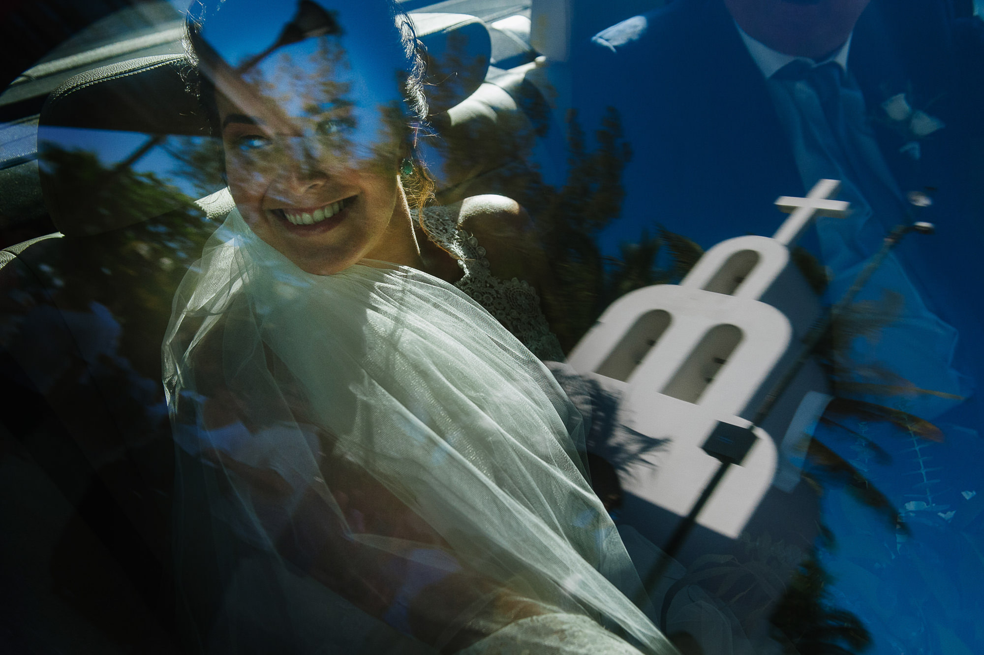 Bride and groom in limo with church reflection, by Citlalli Rico
