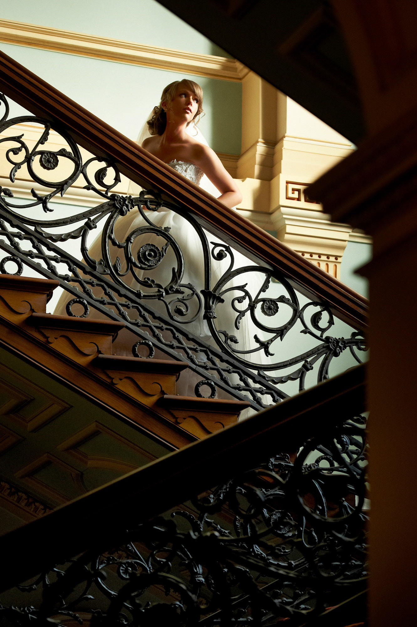 Bride walks up elegant wrought iron stairway photo by Jerry Ghionis