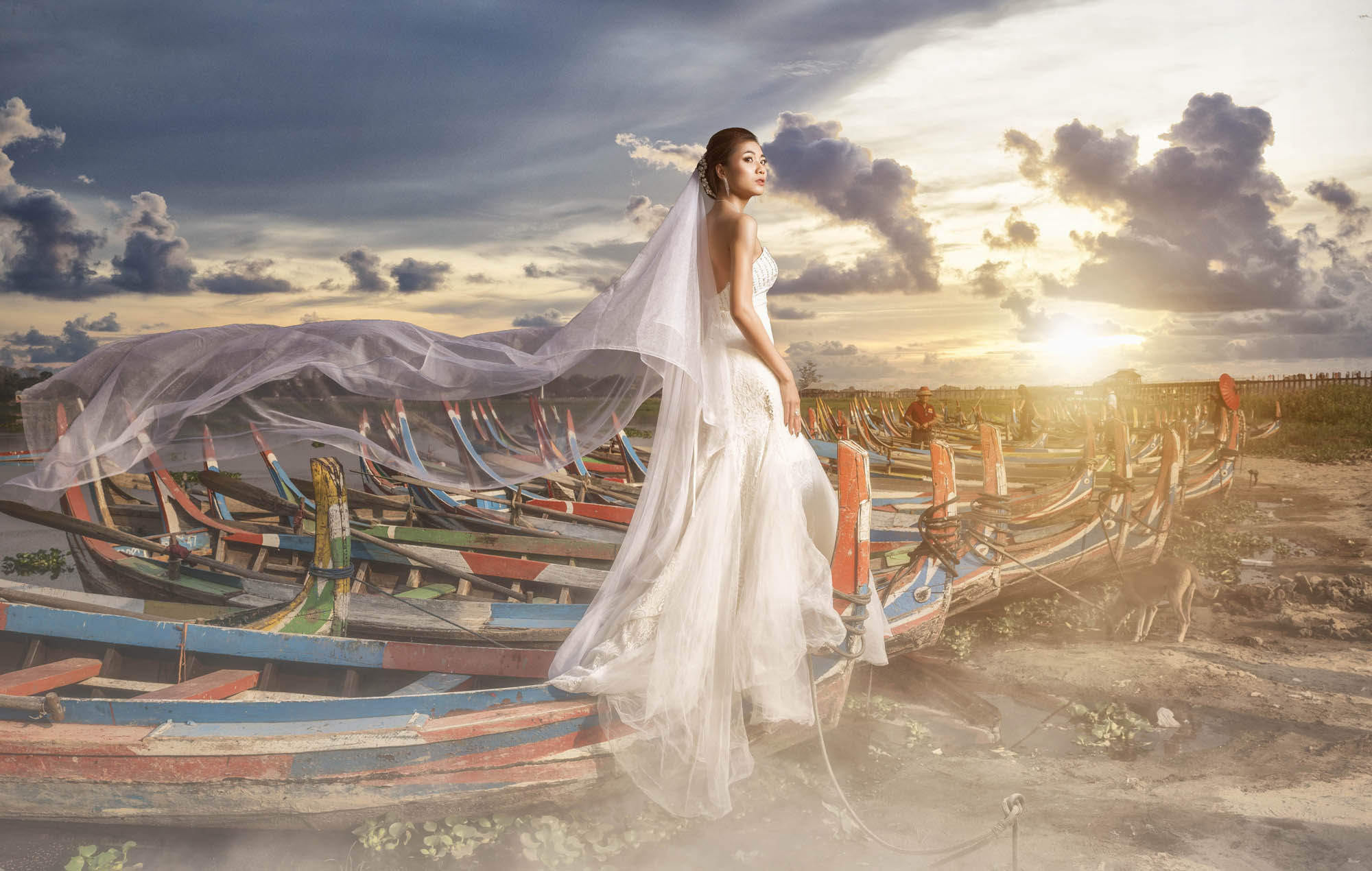 Bride in beautiful chiffon and tulle gown standing on fishing boats, by CM Leung