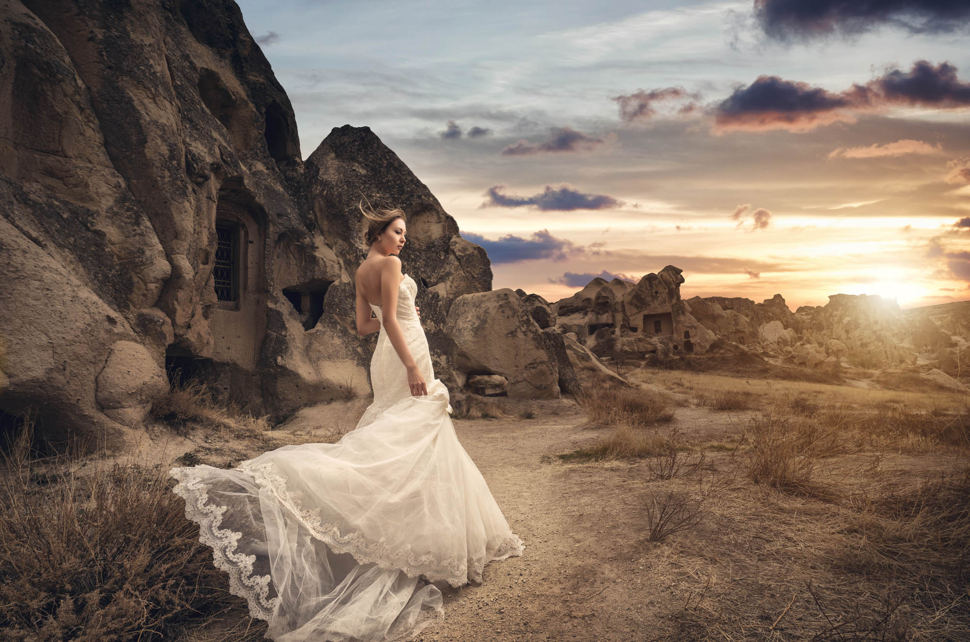 Bride in lace and tulle trumpet gown posing in rocky desert landscape, by CM Leung