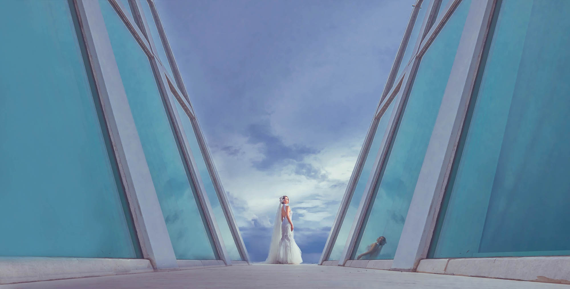 Bride standing between towering glass windows, by CM Leung
