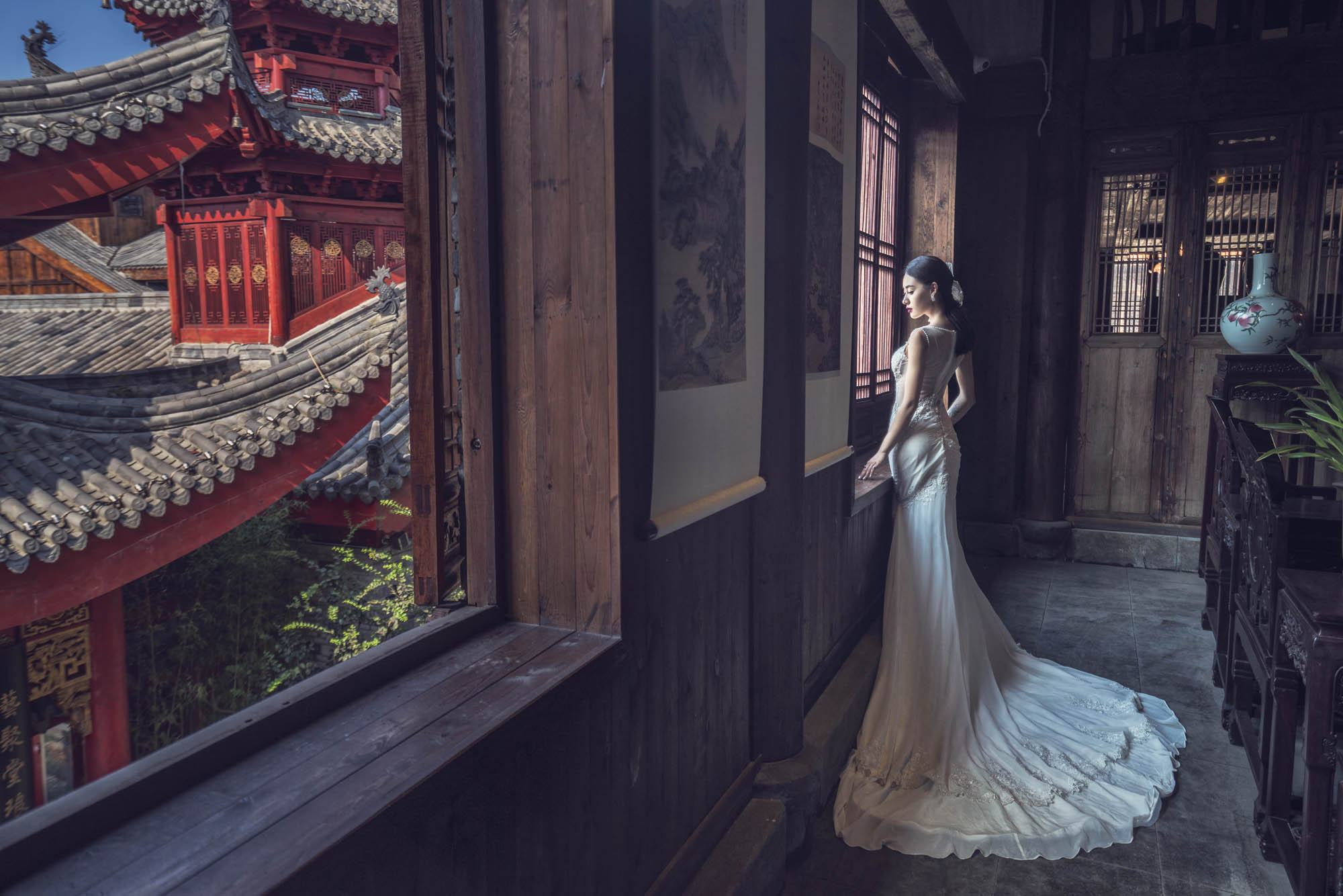 Bride in satin or crepe gown standing in Chinese temple, by CM Leung