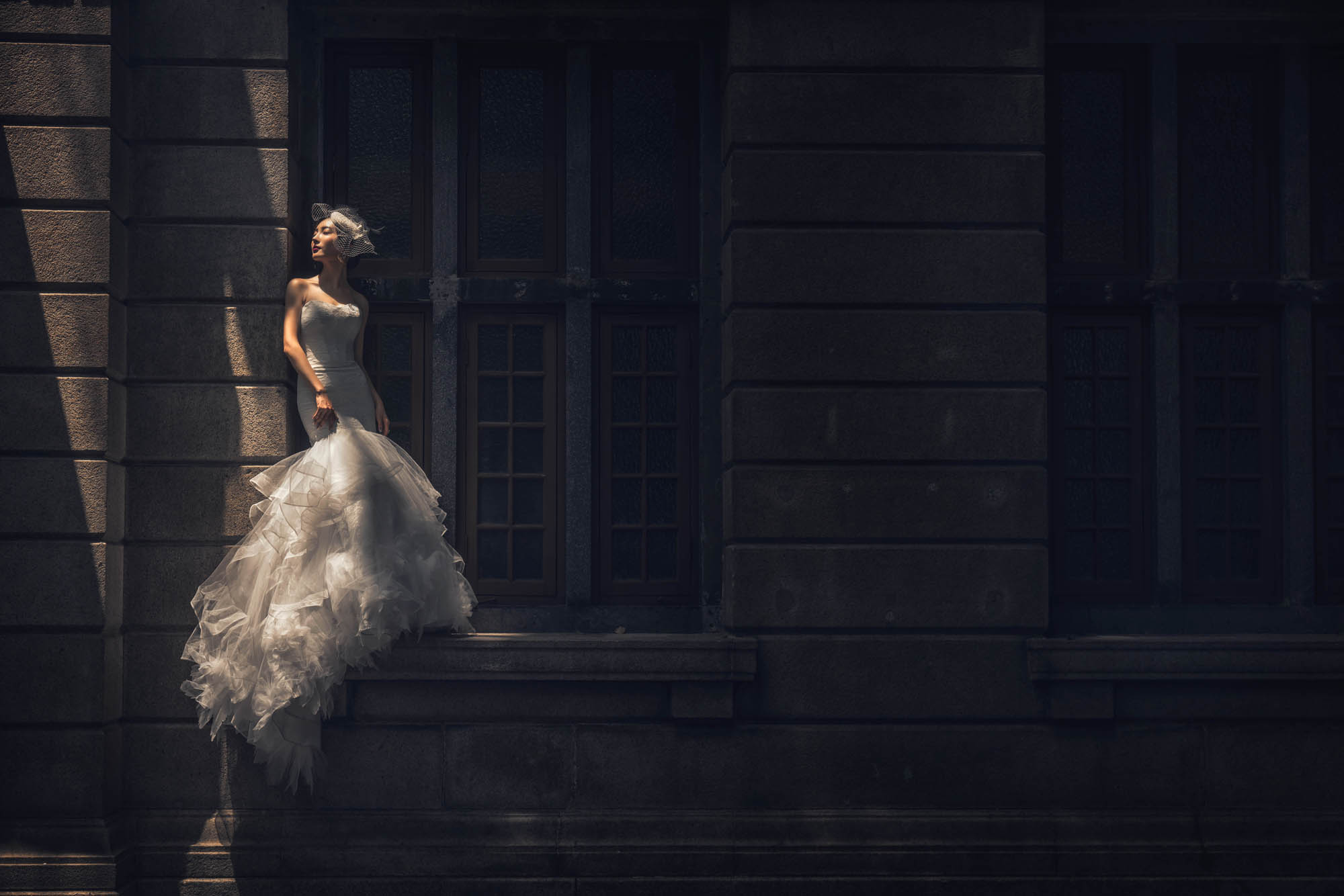 Bride in lace tulle trumpet gown standing on window sill, by CM Leung