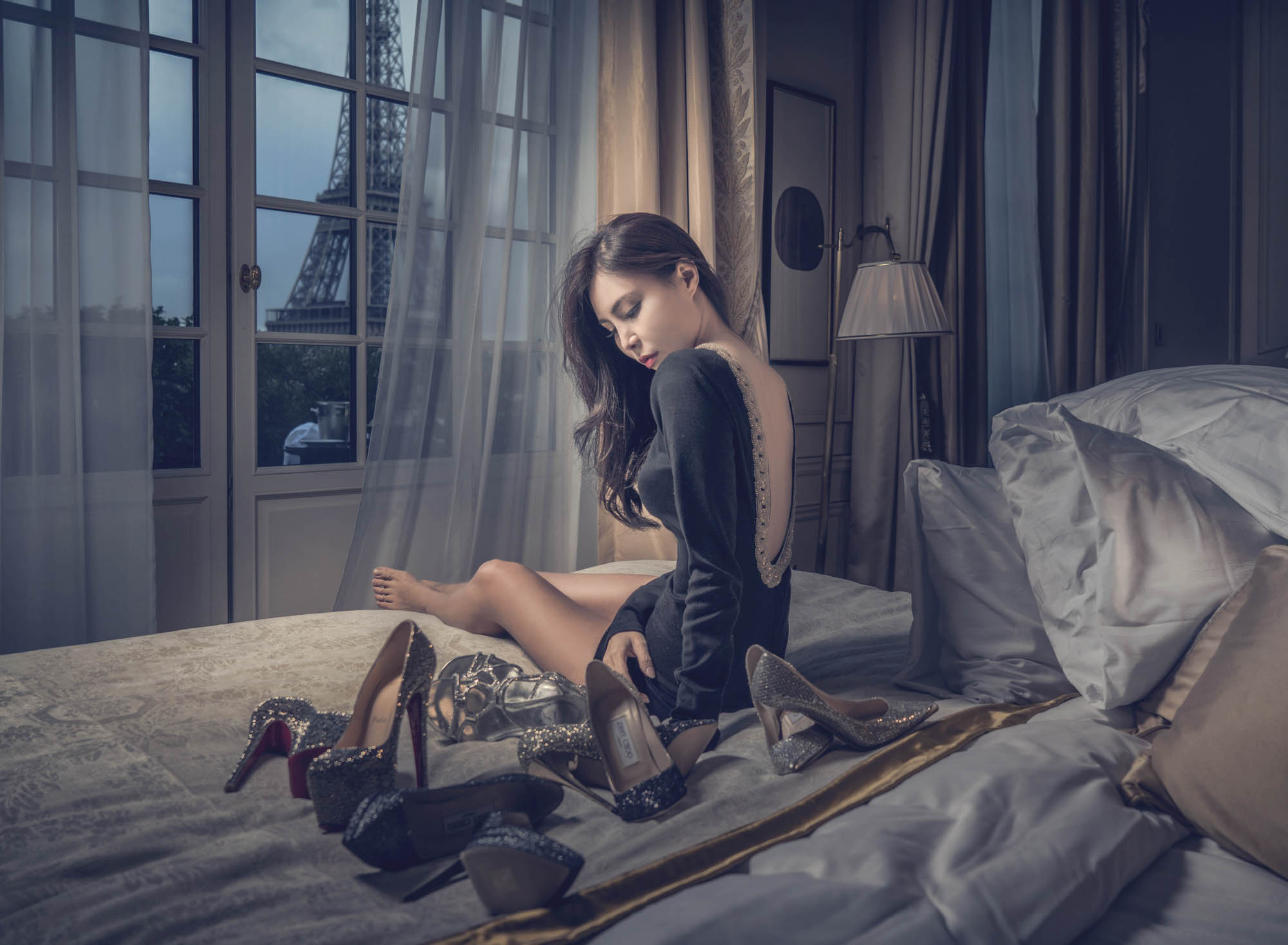 Bride in black backless short dress sitting on bed with shoes, by CM Leung