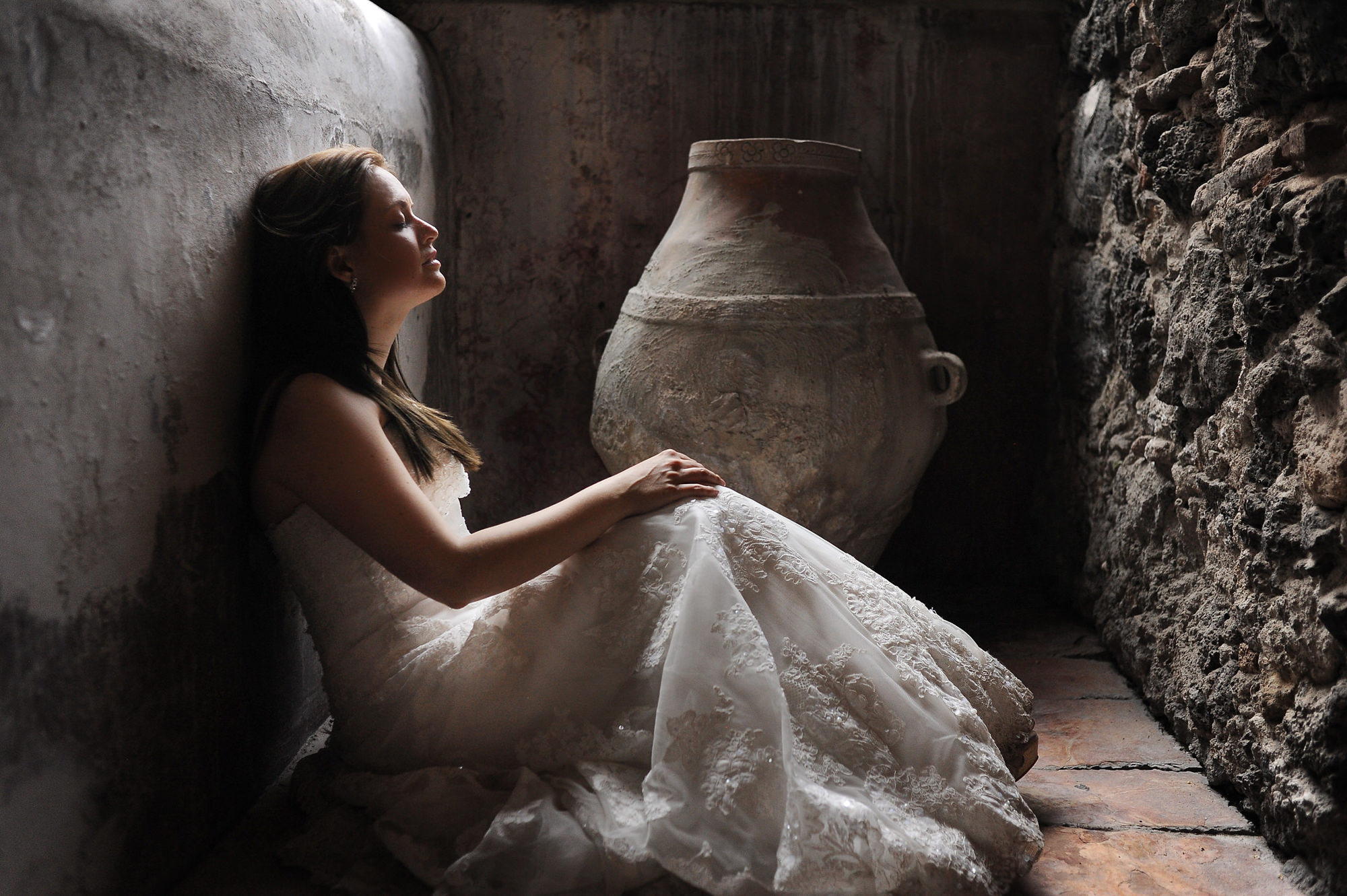 Bride resting in stone room - Daniel Aguilar Photographer