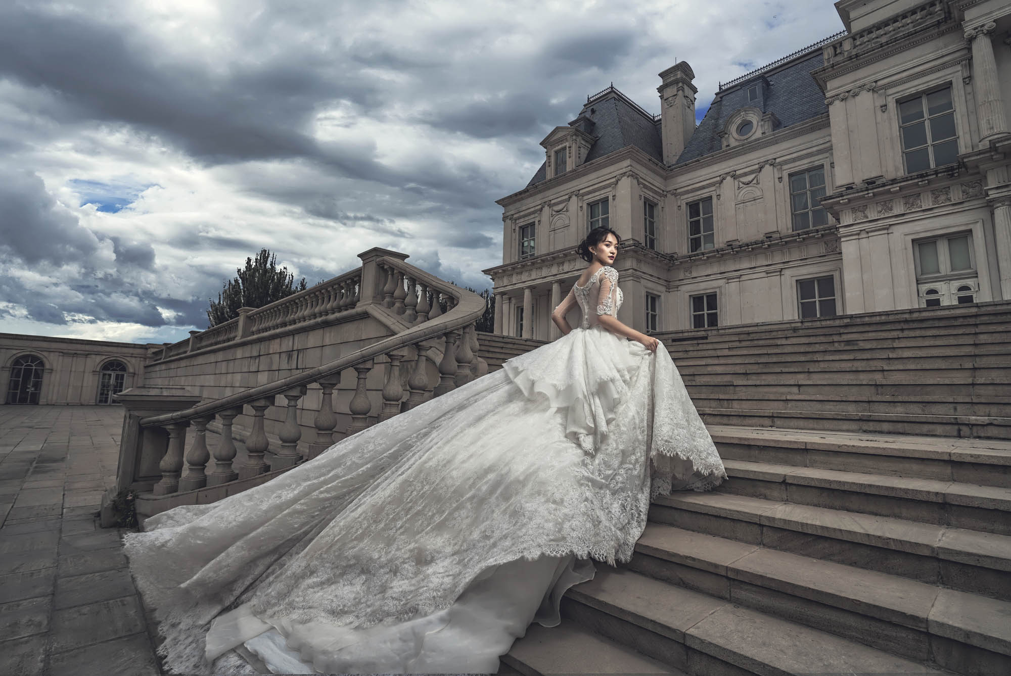 Bride in dramatic princess ballgown ascending stairs at a French chateau, by CM Leung